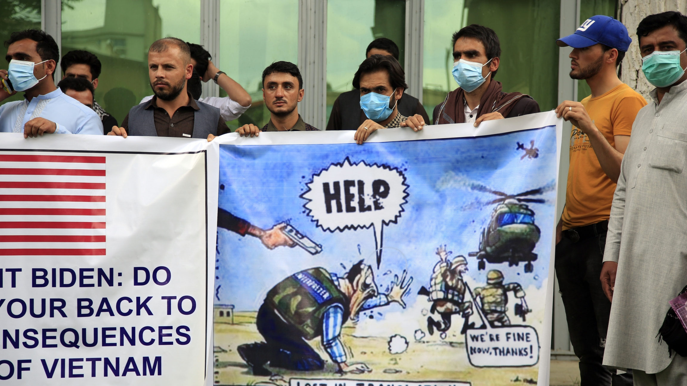 In this Friday, April 30, 2021, file photo former Afghan interpreters hold banners during a protest against the US government and NATO in Kabul, Afghanistan.