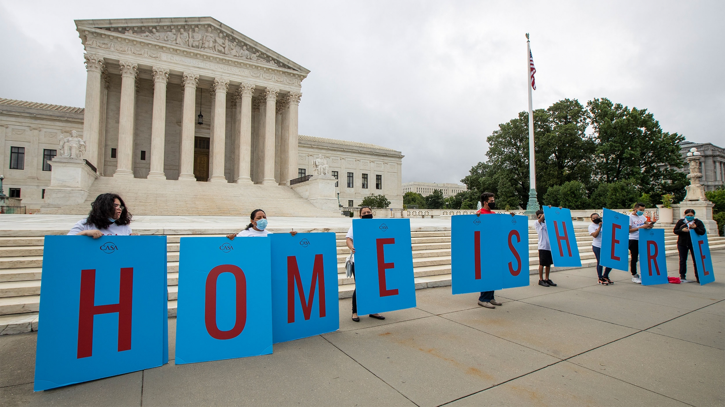 """Students stand in a line in front of the US Supreme Court with signs that read """"Home is here"""""""
