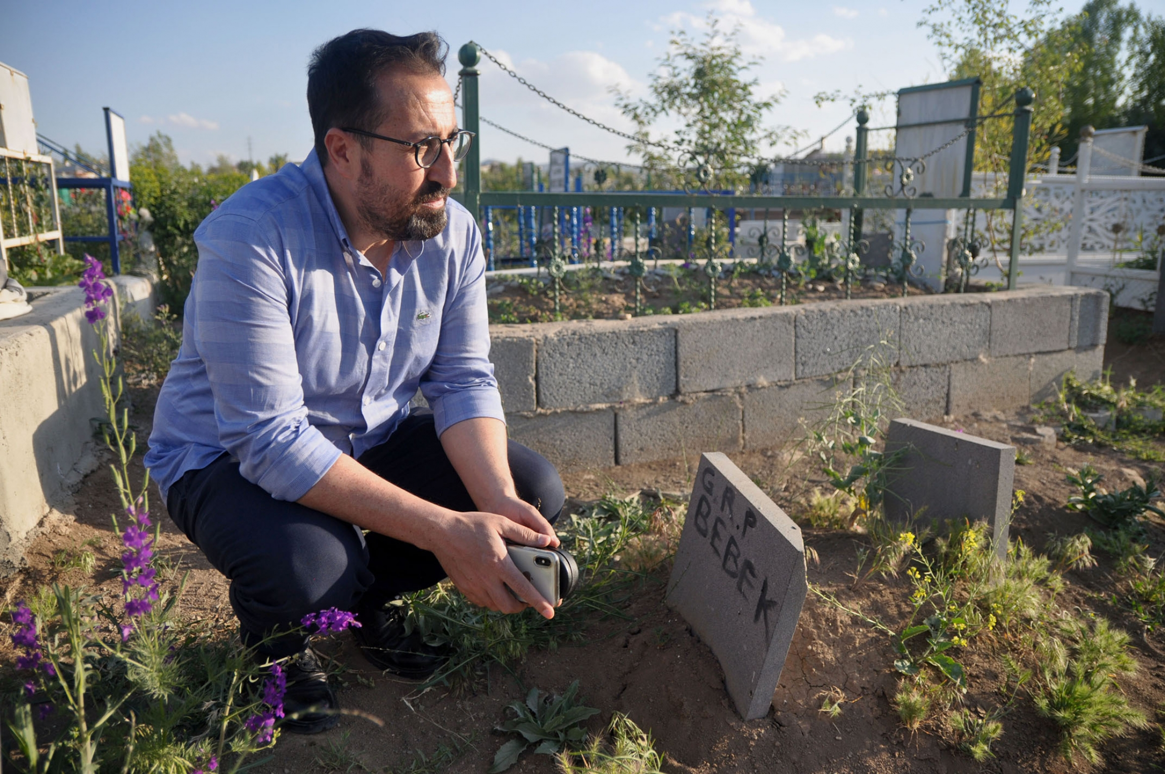Mahmut Kaçan, an attorney with the Van Bar Association, sits near a grave for an infant who died on the journey to Turkey.