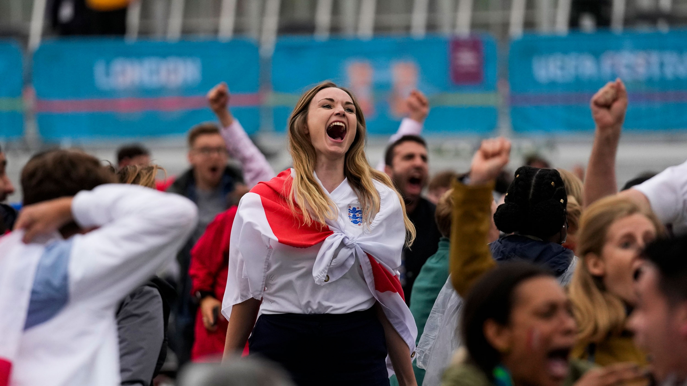 A large crowd of people are shown with a woman in the center of the photograph cheering with her mouth open and an England flag draped on her shoulders.