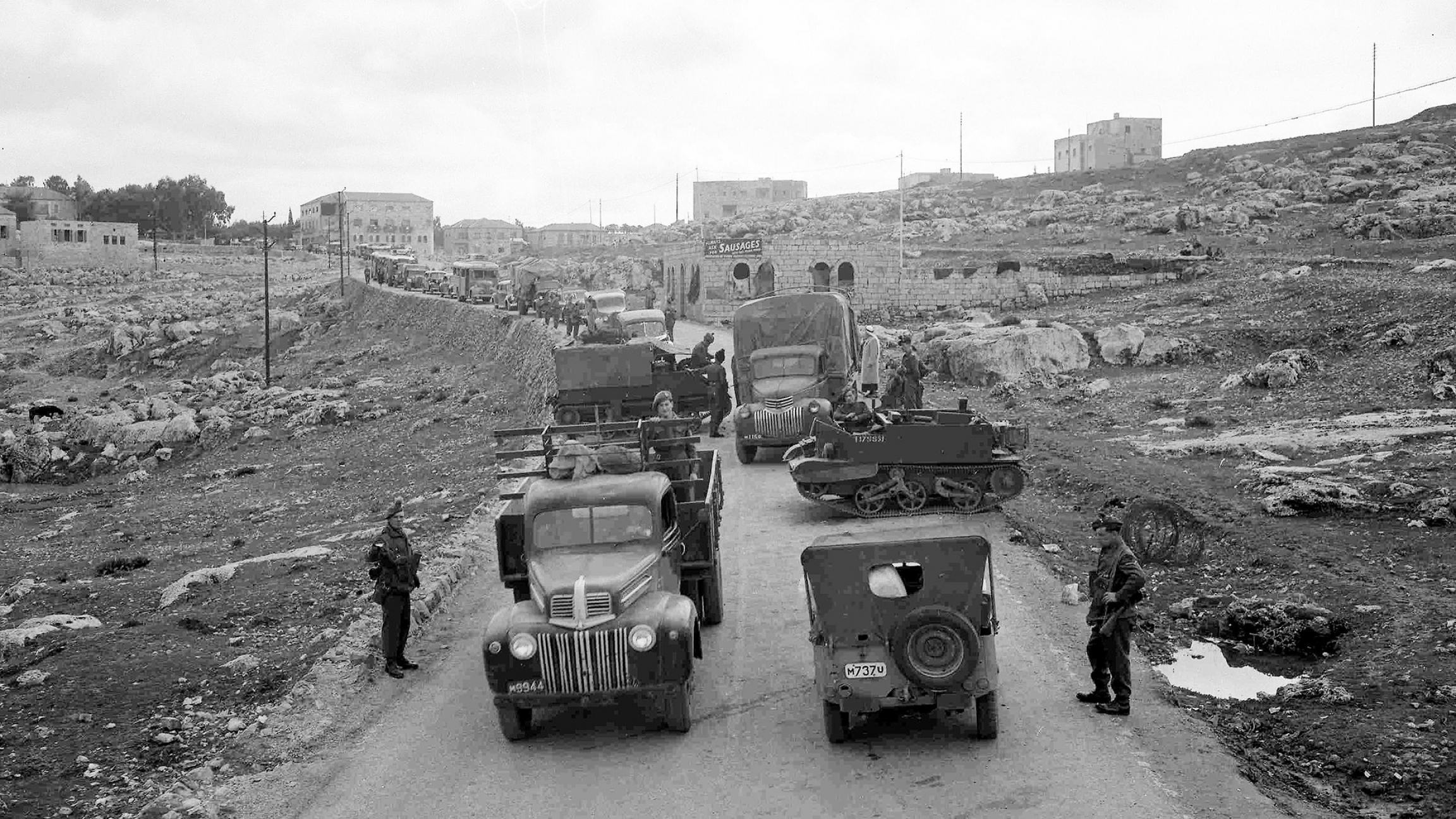 A line of vehicles, stretching for almost a mile, waits to pass through a road block on the main road from Jerusalem to Tel Aviv, Feb. 6, 1947. The road block is manned by members of the Royal Irish Fusiliers.