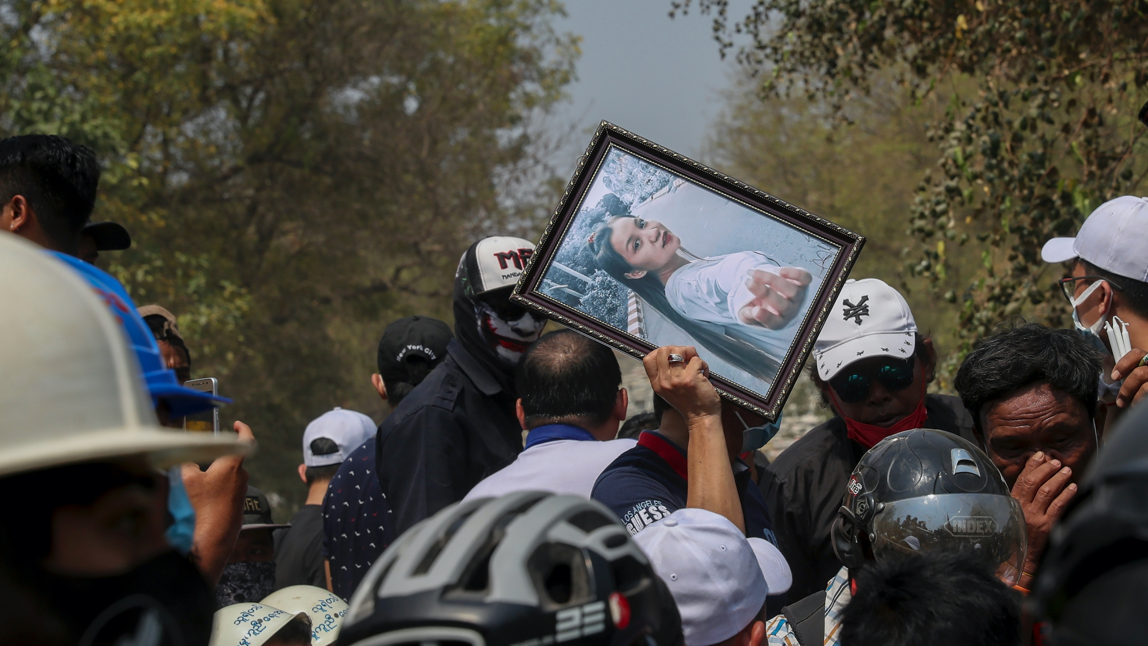 A man holds a picture of 19-year-old Kyal Sin, also known as Angel, during her burial in Mandalay, Myanmar