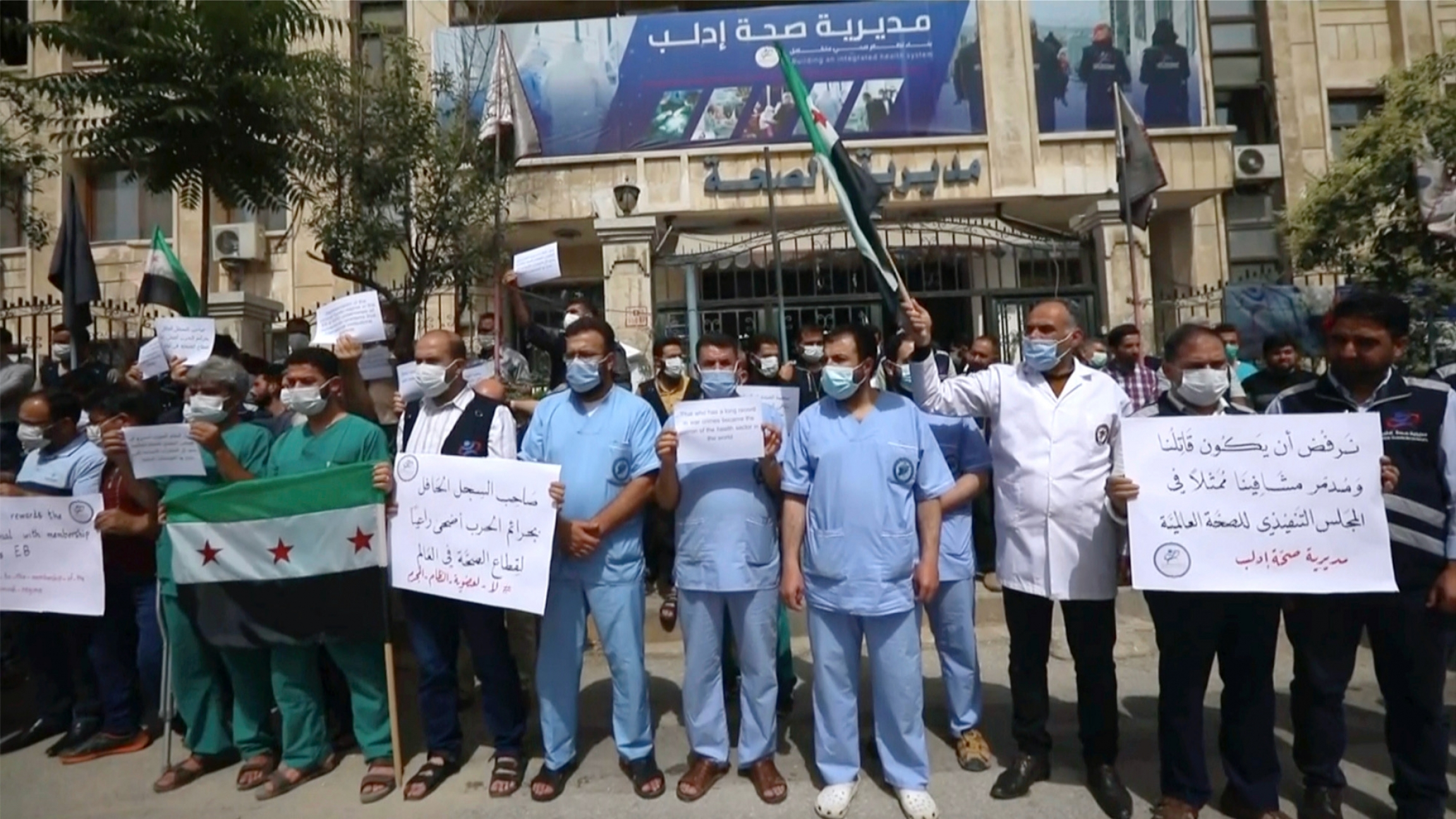 In this image taken from video, dozens of medical workers protest a decision to grant Syrian President Bashar al-Assad's government a seat on the executive board of the World Health Organization, May 31, 2021, in Idlib, Syria.
