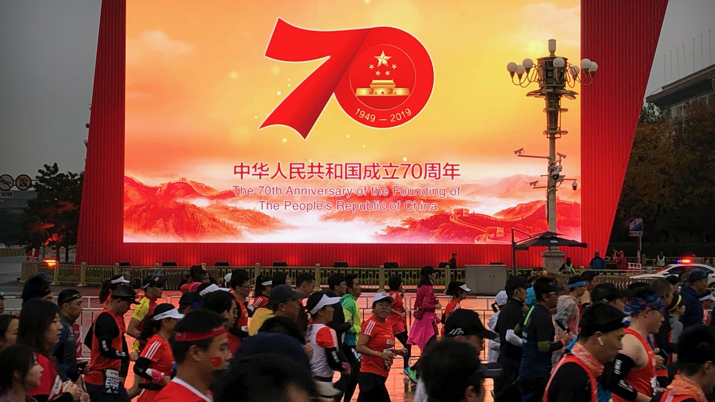 Runners pass by a large video screen commemorating the 70th anniversary of the founding of Communist China during the Beijing Marathon in Beijing, Nov. 3, 2019.