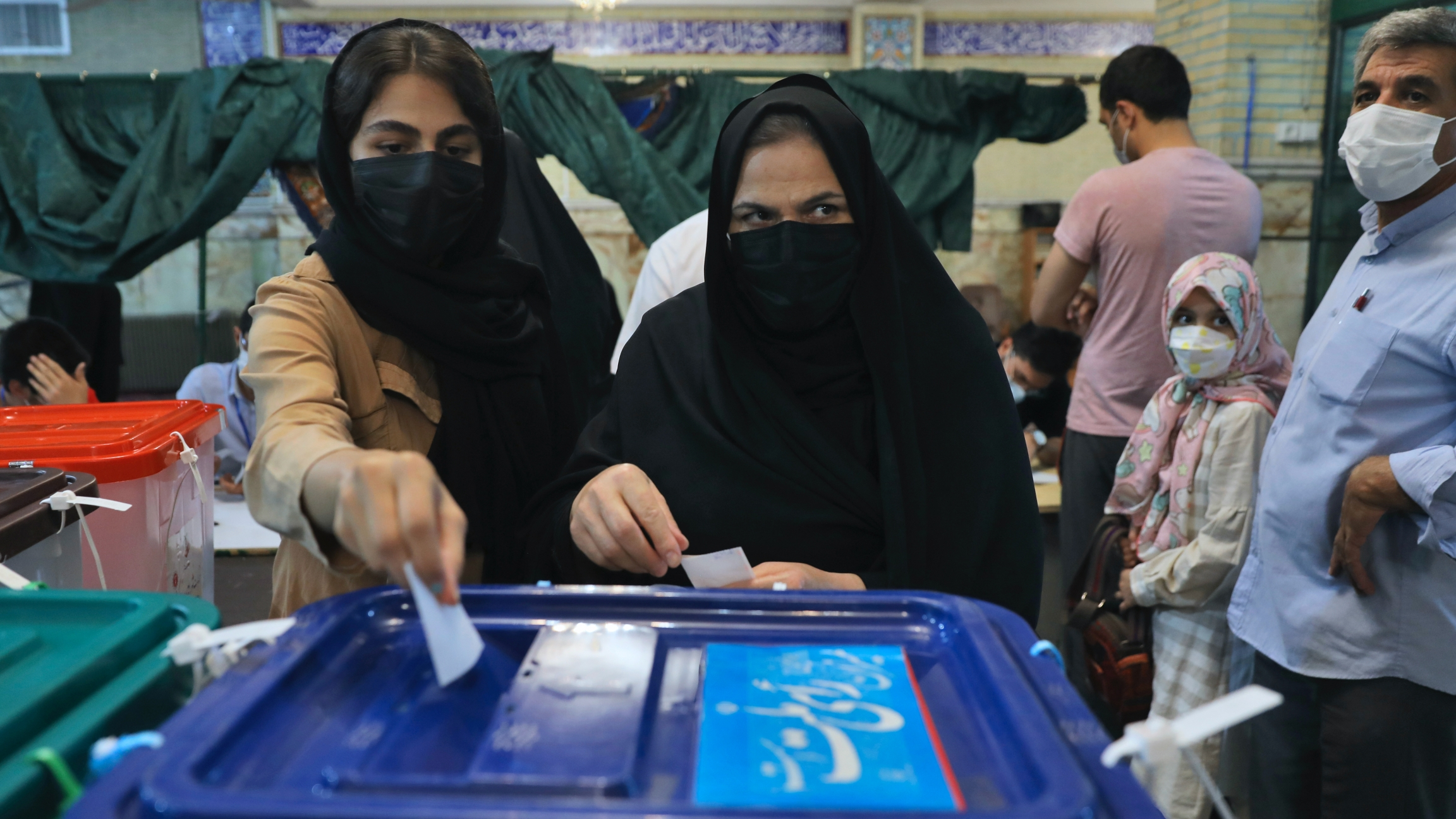 Voters cast their ballots for the presidential elections at a polling station in Tehran, Iran, June 18, 2021.