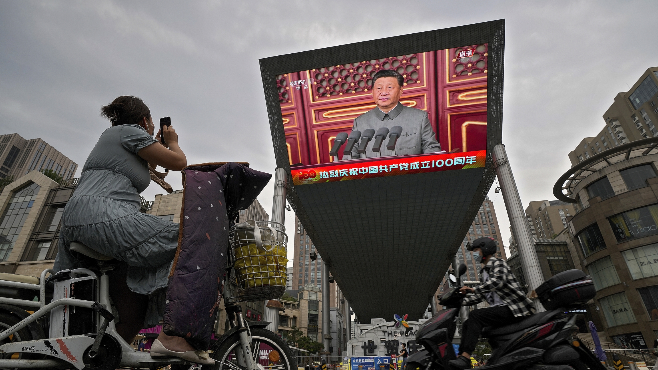 A woman on her electric-powered scooter films a large video screen outside a shopping mall showing Chinese President Xi Jinping speaking during an event to commemorate the 100th anniversary of China's Communist Party at Tiananmen Square in Beijing.