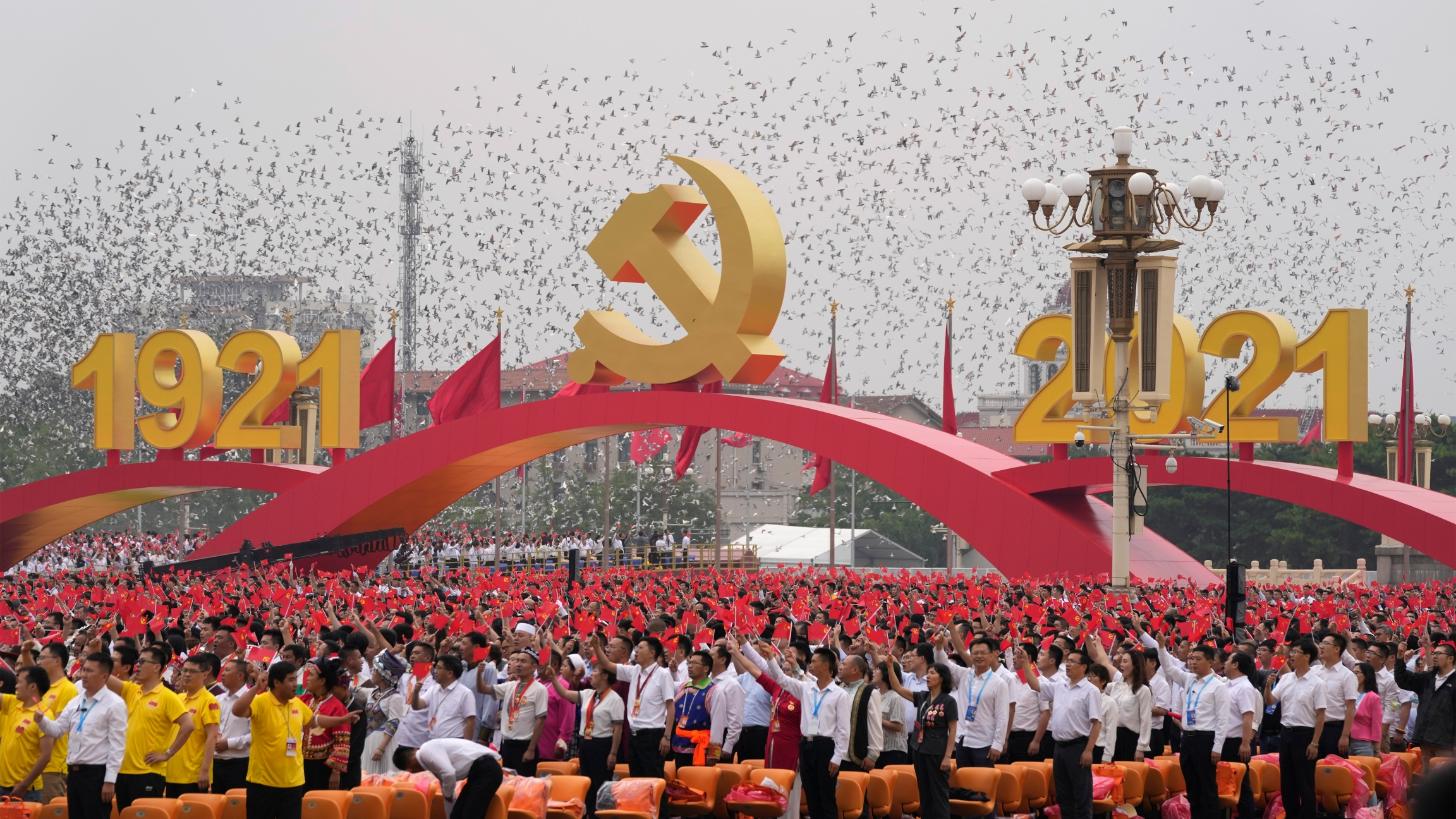 Attendees wave Chinese flags during a ceremony at Tiananmen Square to mark the 100th anniversary of the founding of the ruling Chinese Communist Party in Beijing