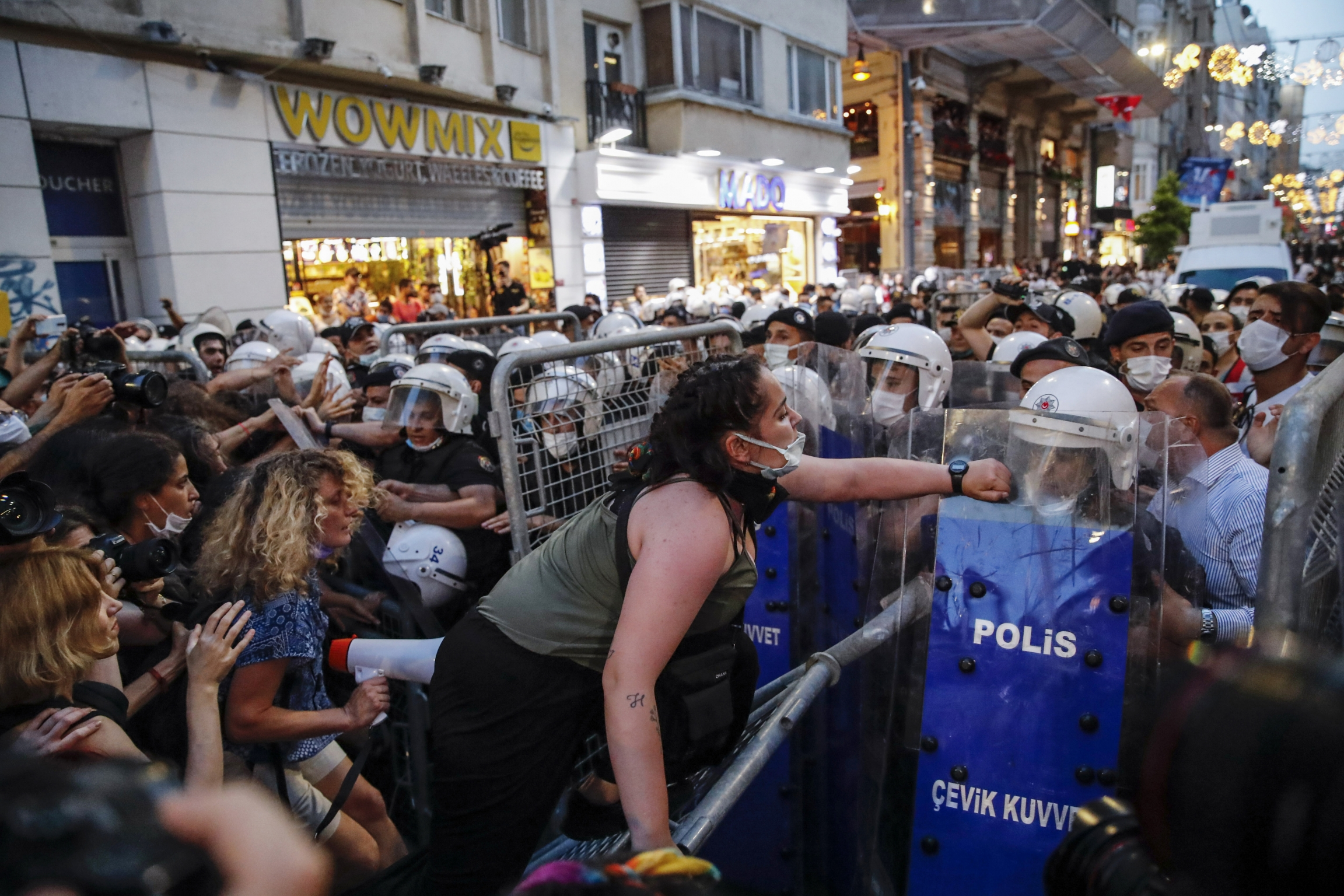 Protesters, left, clash with police officers preventing them from marching against the government's decision to withdraw from Istanbul Convention, in Istanbul, Thursday, July 1, 2021.