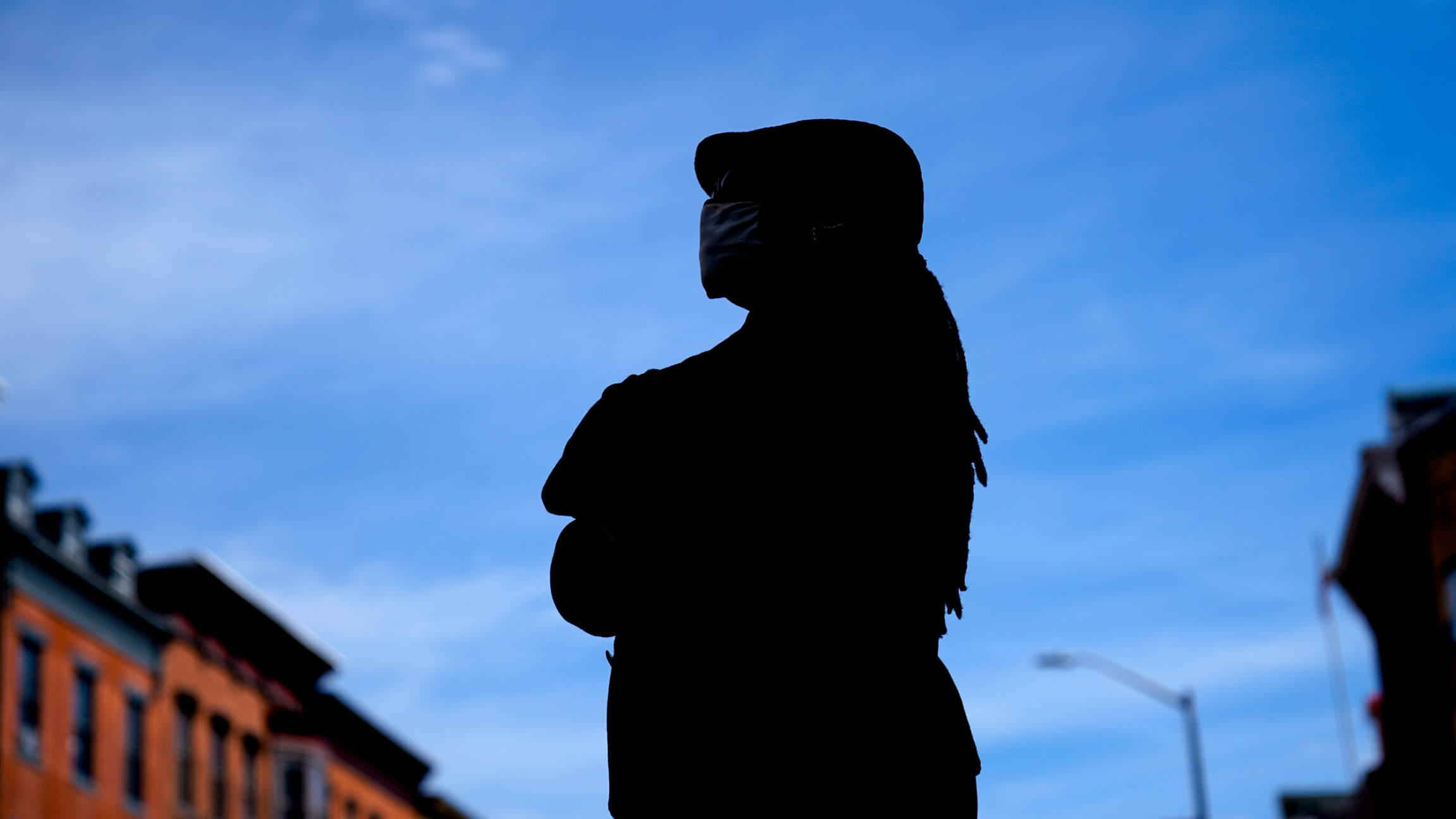A woman stands in silhouette against a blue sky.