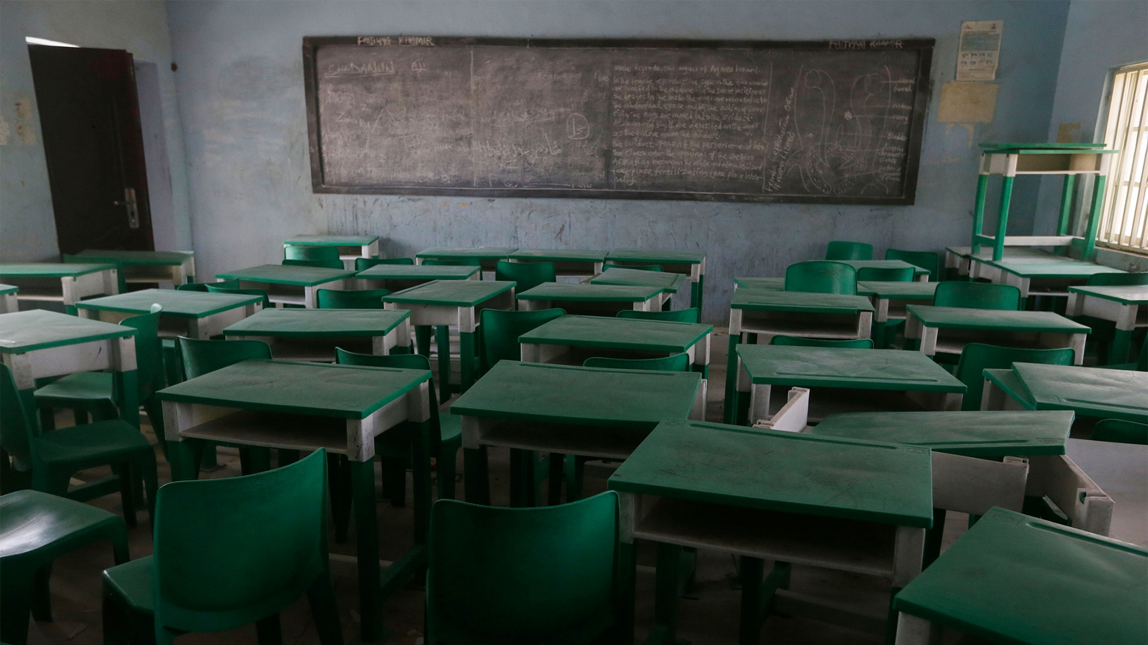 Empty green desks and chairs in a classroom with a chalkboard at the front