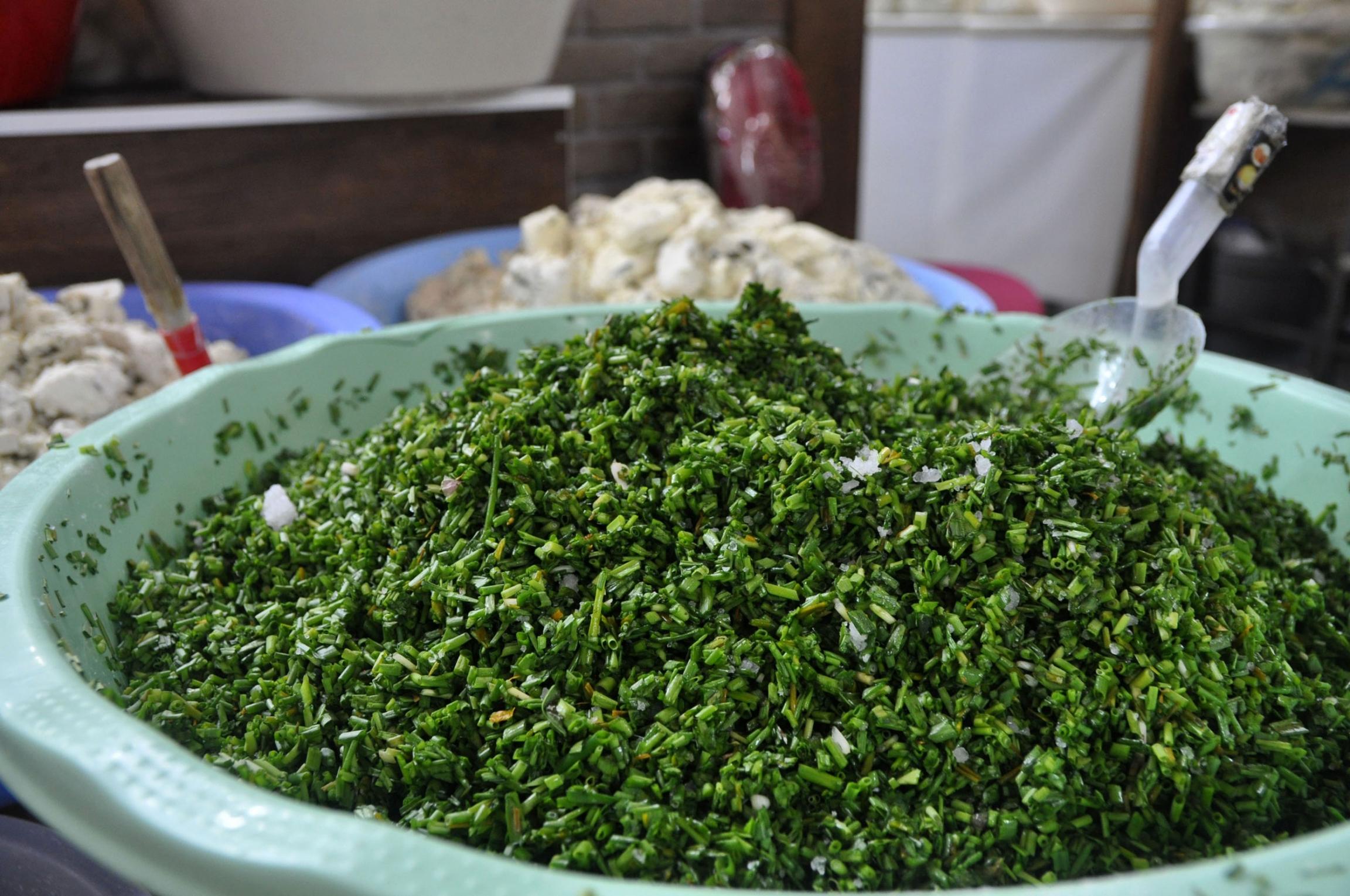 Green herbs used in Van Otlu Peyniri mixed in a green bowl.