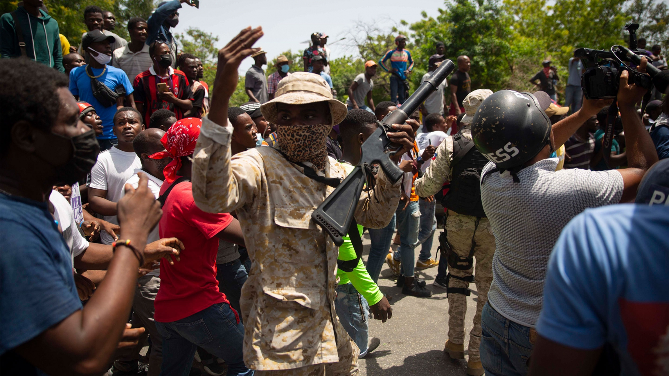 Police in camouflage stand amid a crowd protesting against the assassination of Haitian President Jovenel Moïse