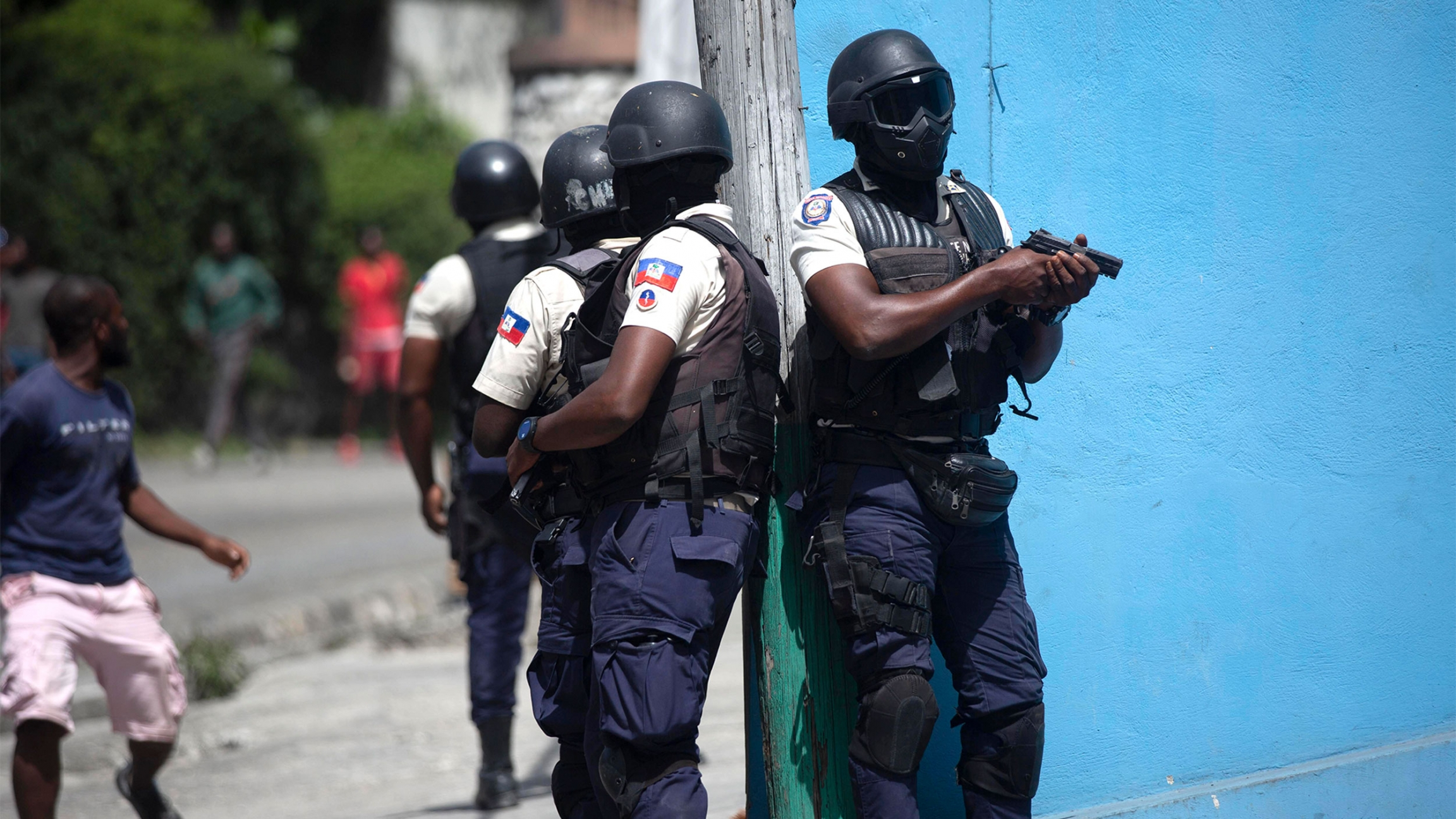Police officers with guns drawn patrol the streets of Haiti