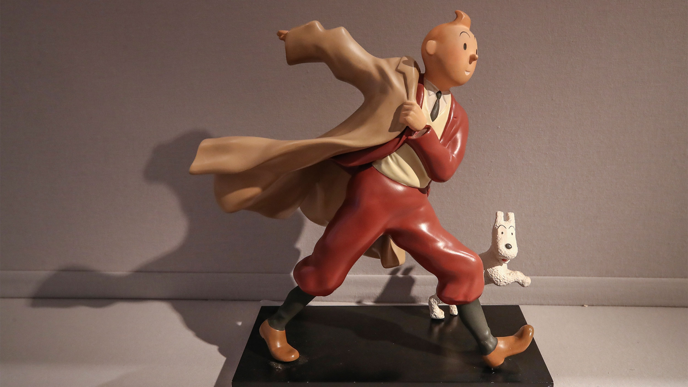 A 1988 polychrome resin sculpture is displayed of the comic character Tintin and his dog snowy