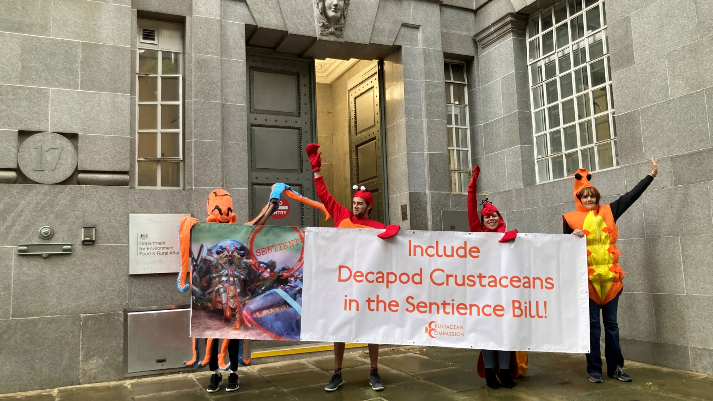 Activists dressed in shellfish costumes cheer with a banner.