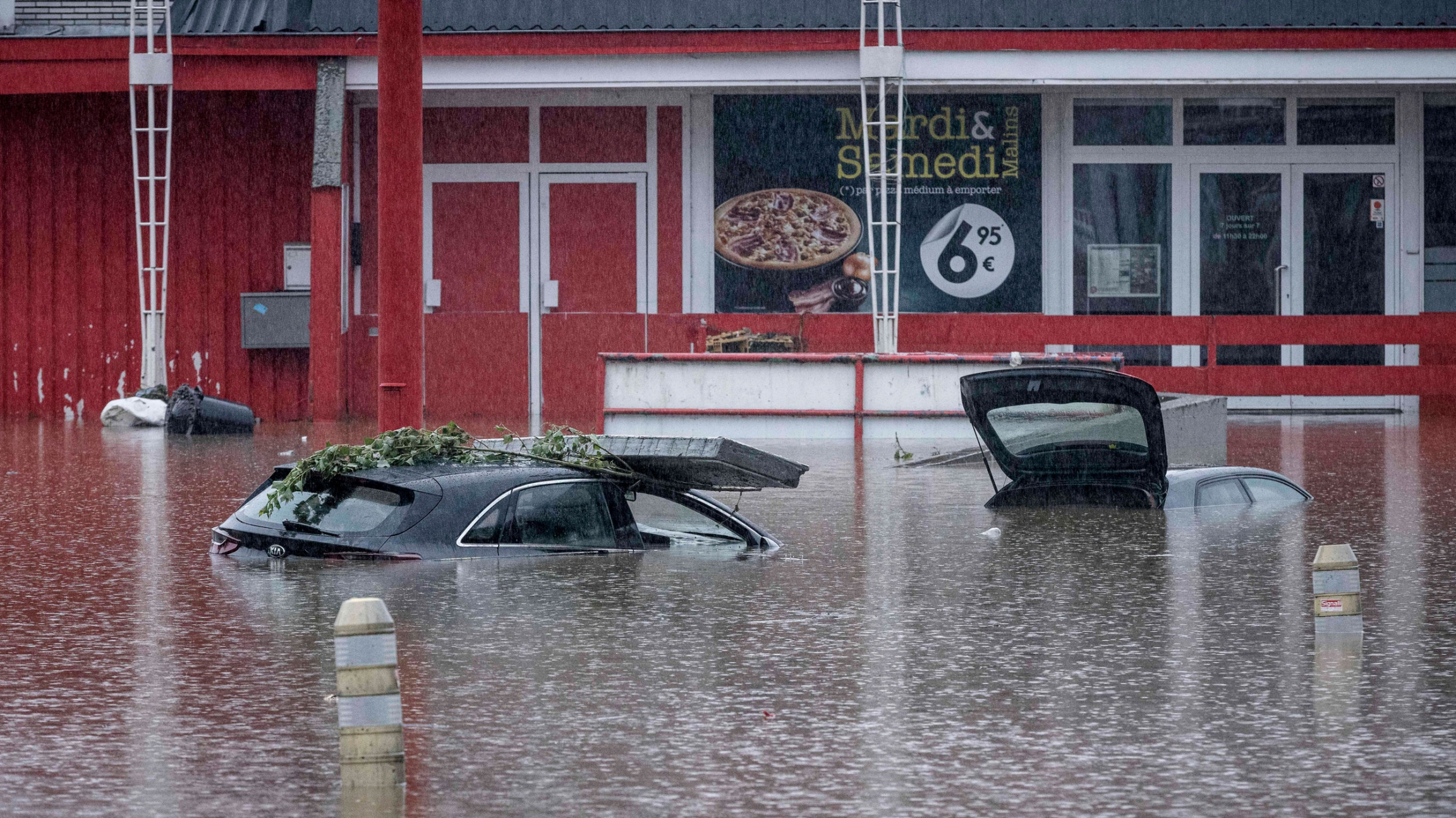 Cars are submerged in water after the Meuse River broke its banks during heavy flooding in Liege, Belgium, Thursday, July 15, 2021.