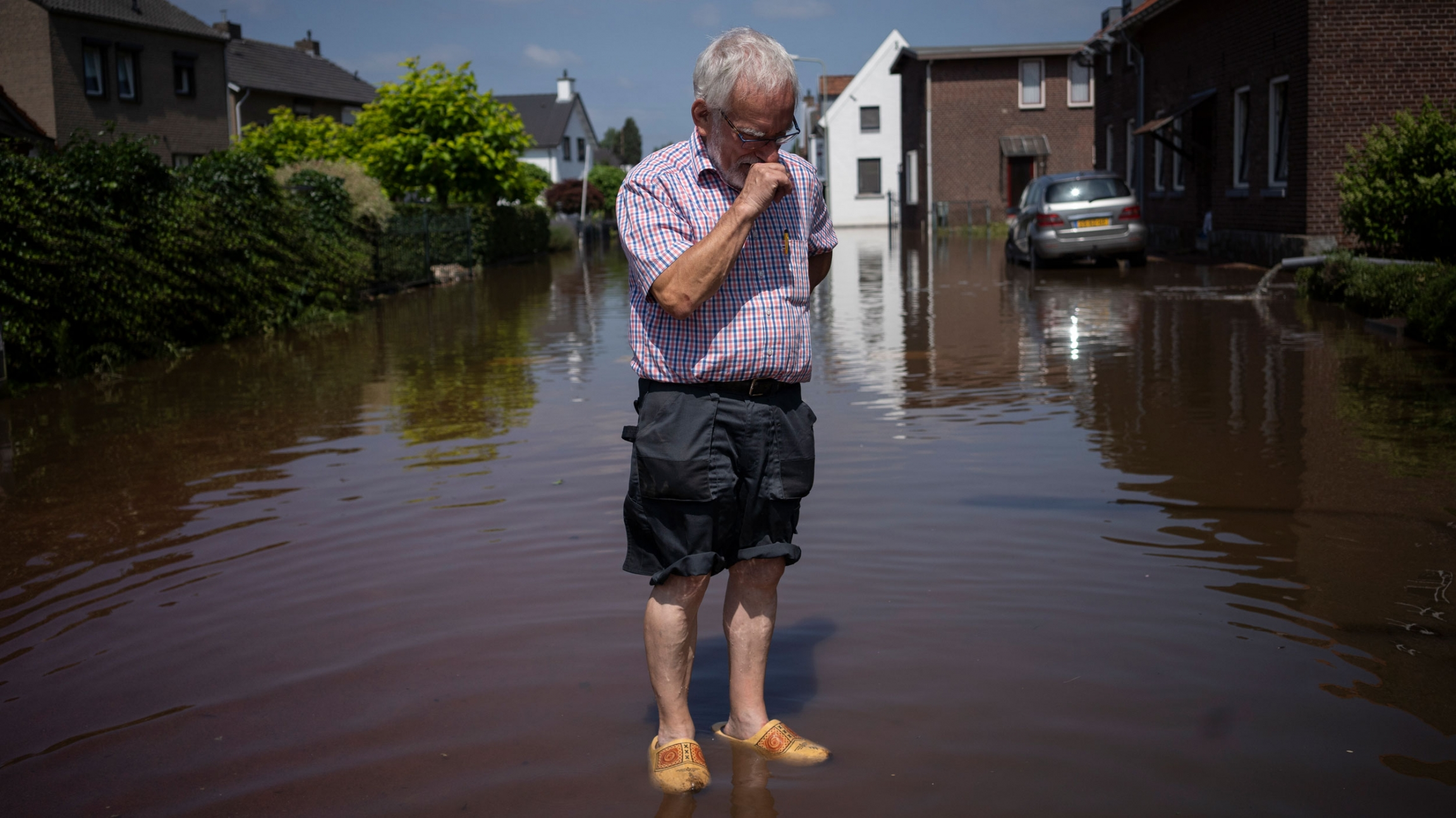 Wiel de Bie, 75, stands outside his flooded home in the town of Brommelen, Netherlands, July 17, 2021.
