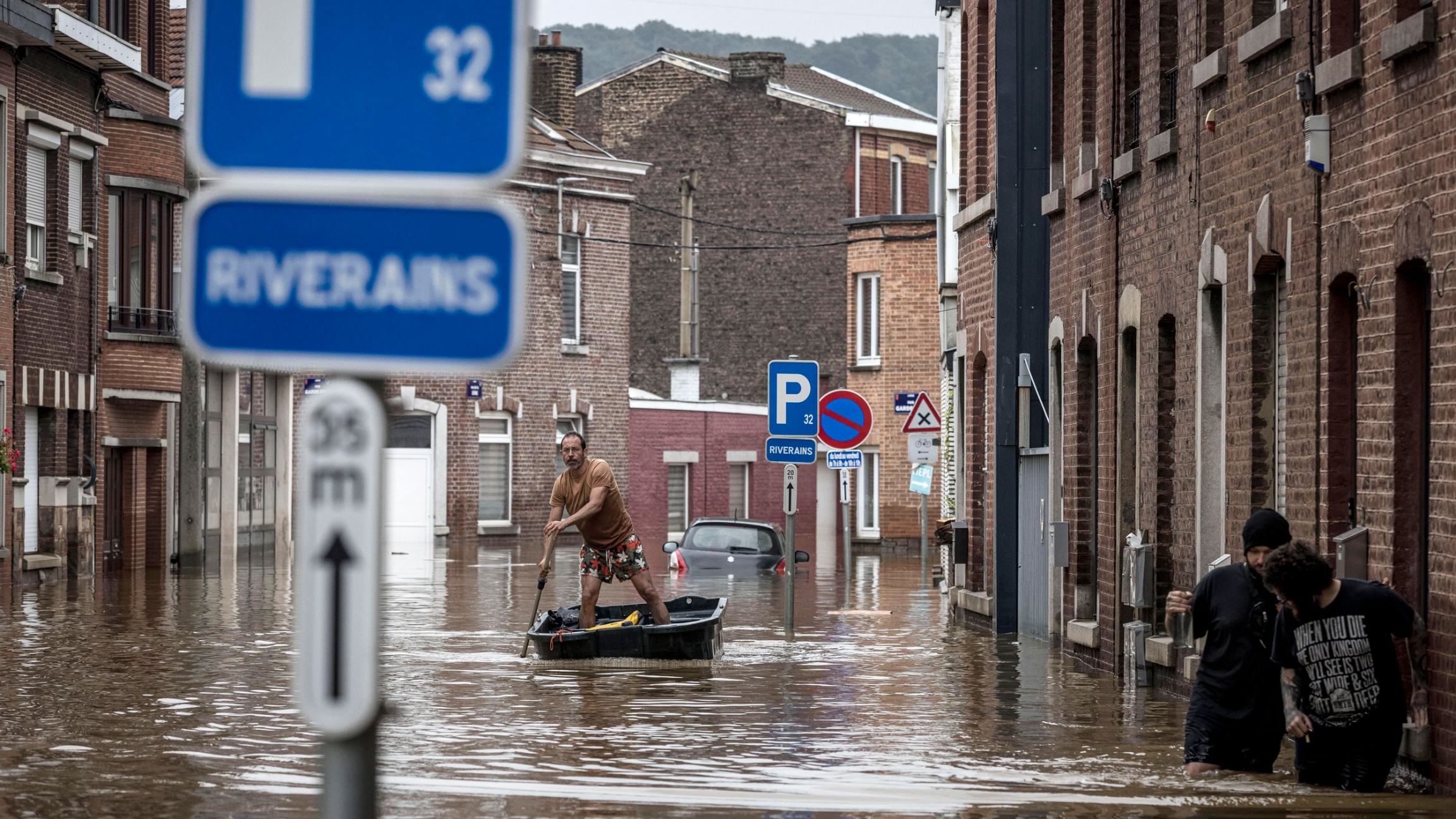 A man is shown standing in a canoe and rowing down an city street flooded by several feet.
