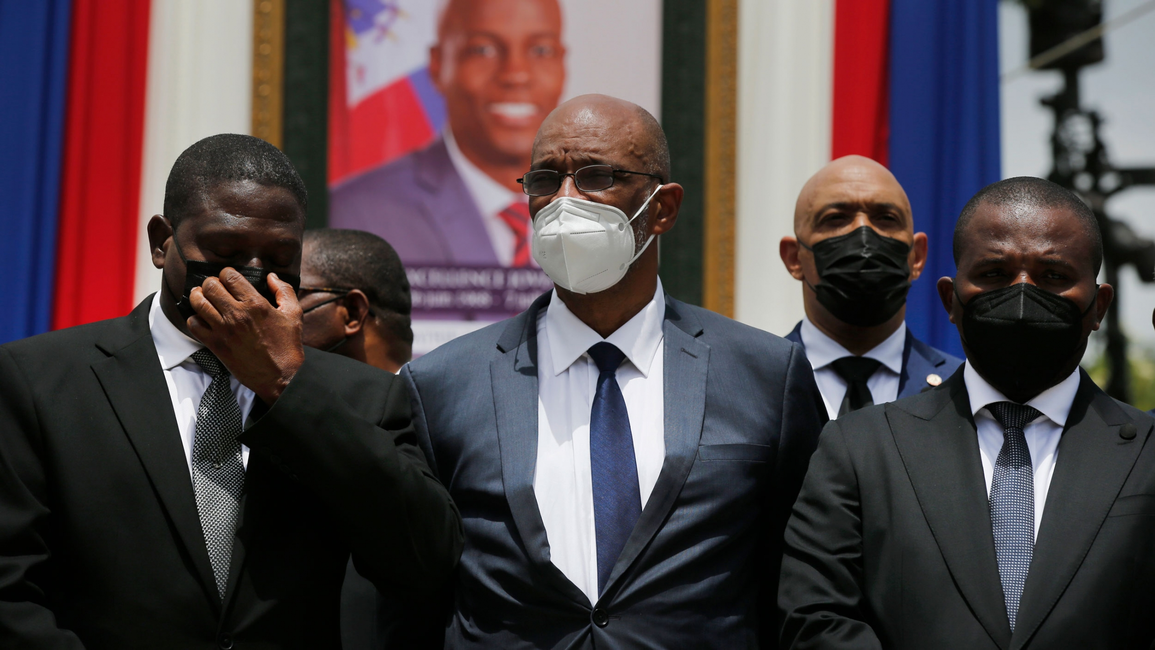 Haiti's designated Prime Minister Ariel Henry, center, and interim Prime Minister Claude Joseph, right, pose for a group photo with other authorities in front of a portrait of late Haitian President Jovenel Moïse at at the National Pantheon Museum during