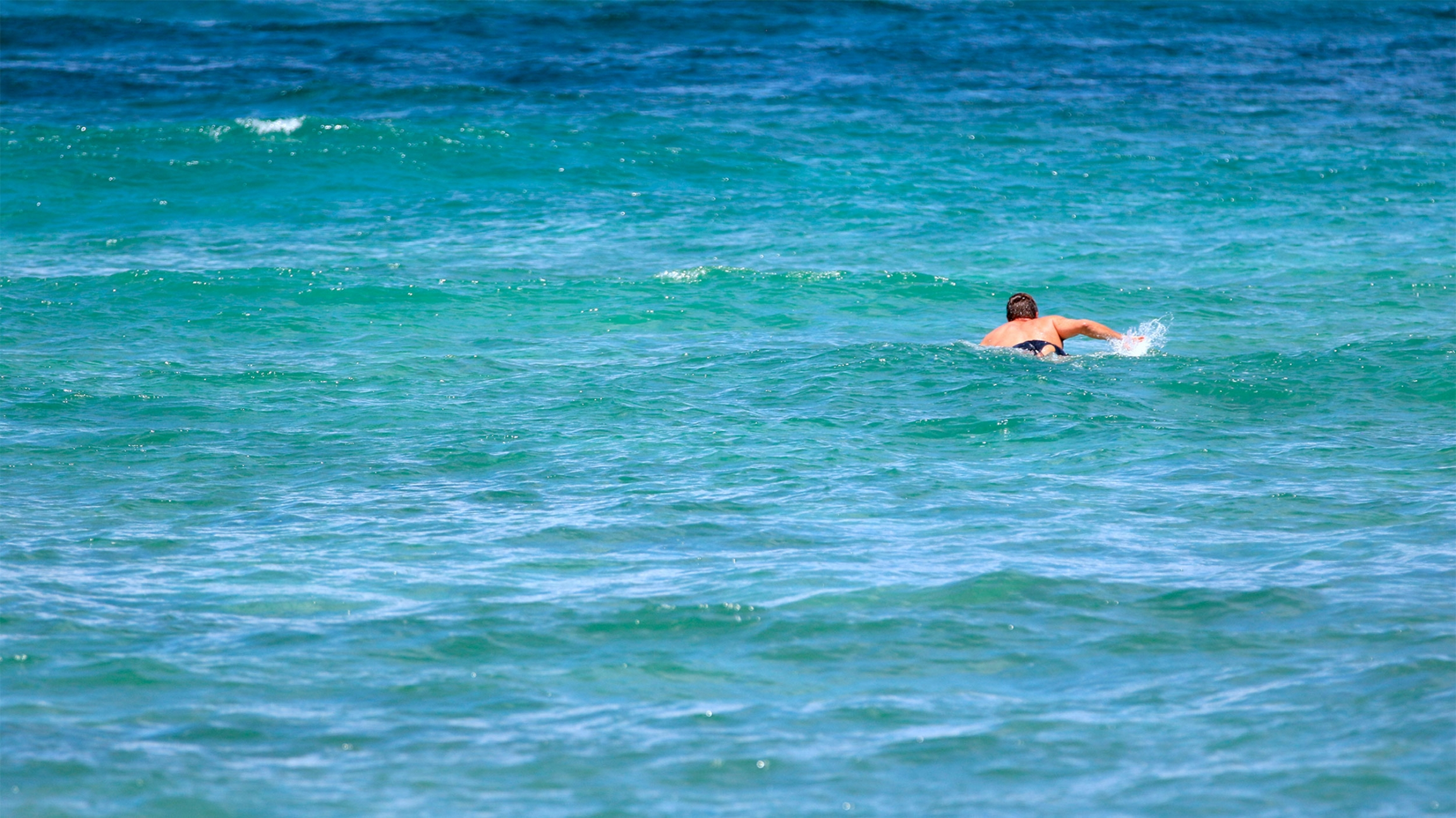 Isaiah Helekunihi Walker paddles out to the blue and green surf in Laie, Hawaii