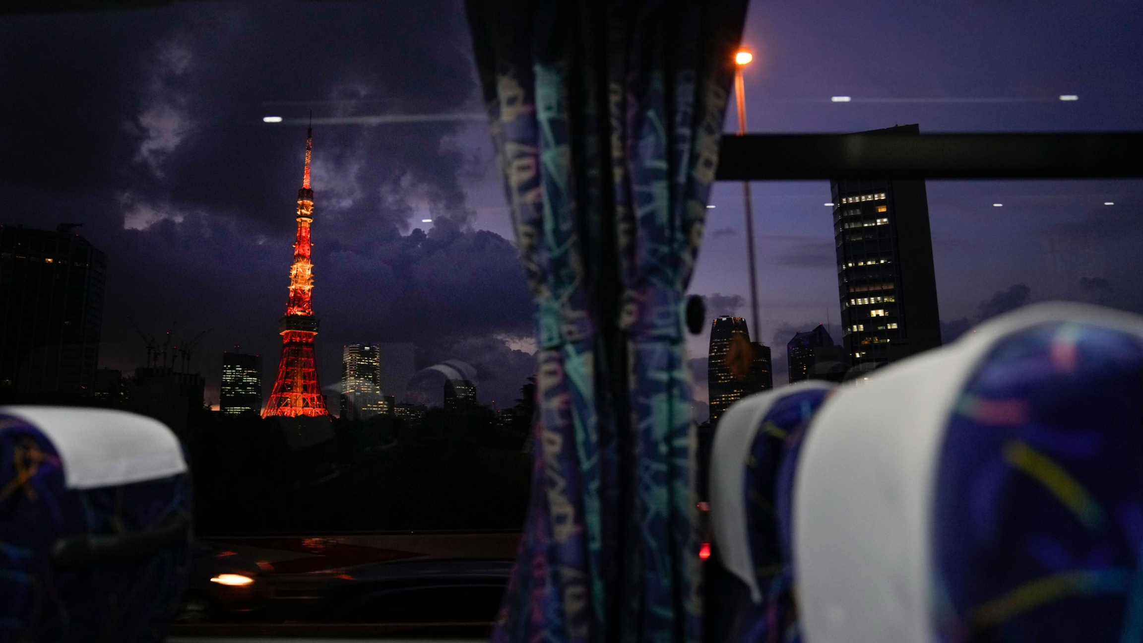 The Tokyo Tower is shown in the distance illuminated with red and orange lighting.