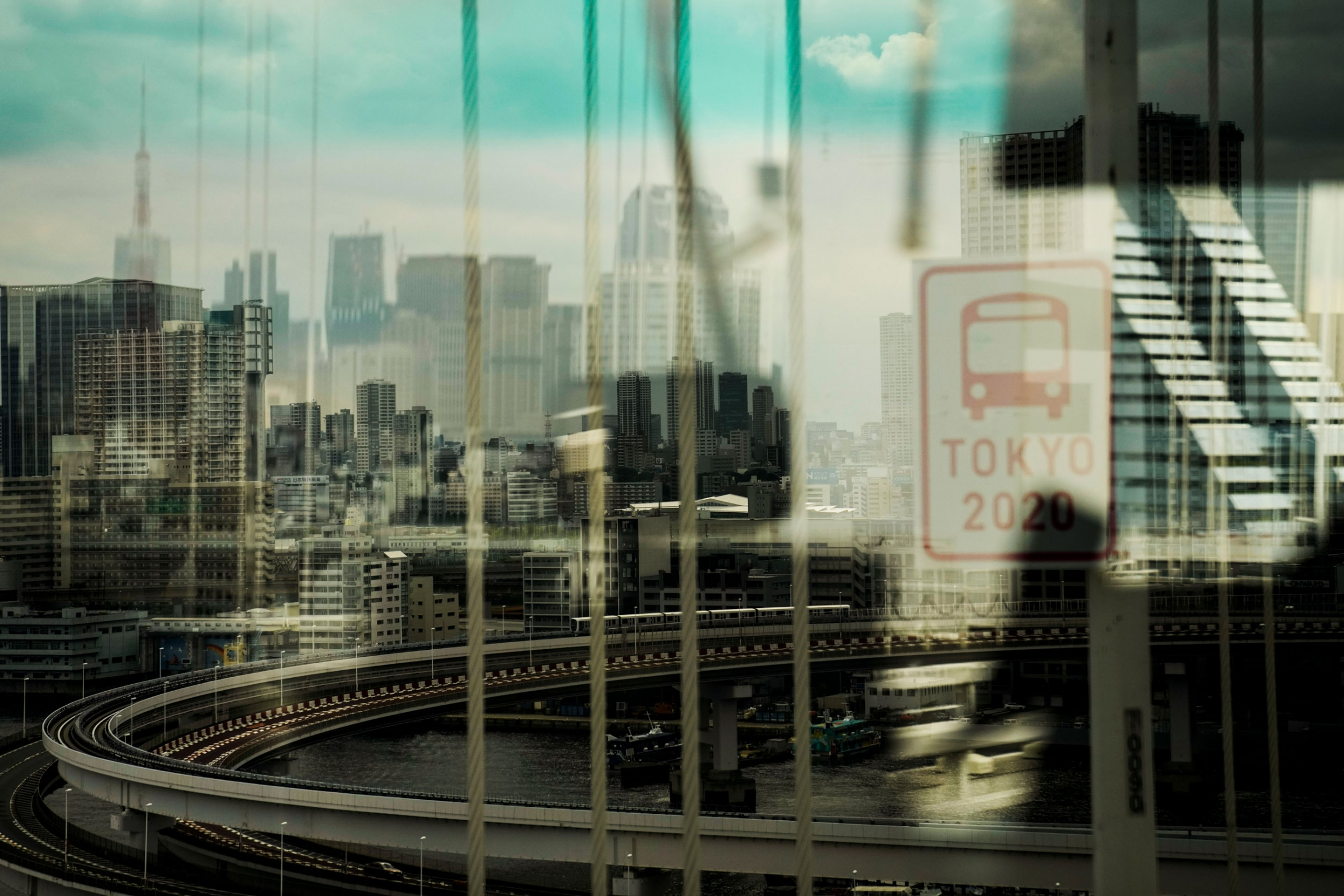 A major roadway and elevated train track along with the Tokyo skyline are shown blurred slightly via a bus window.