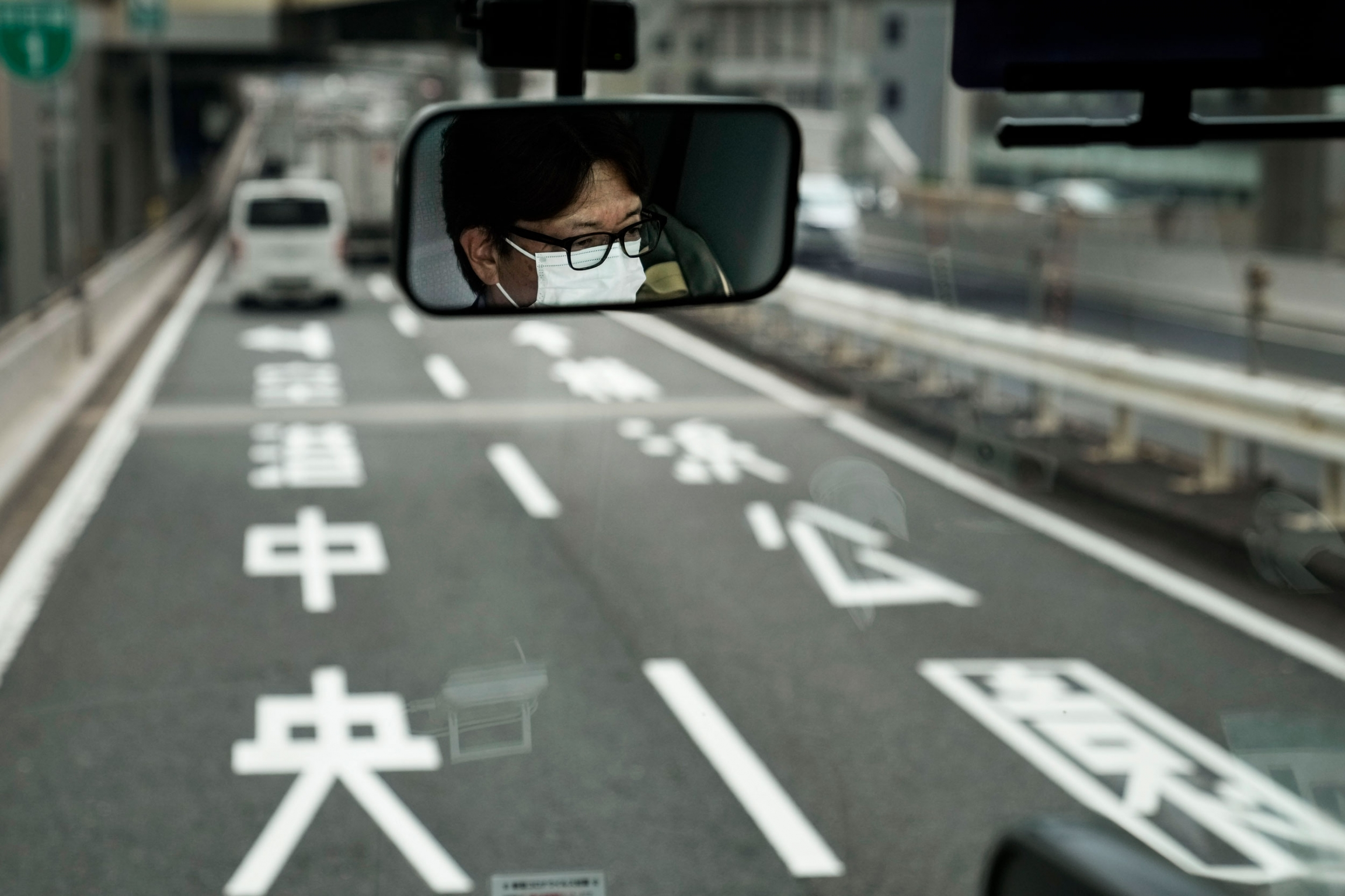 The face of a bus driver is shown covered in a white mask with a two lane road ahead.