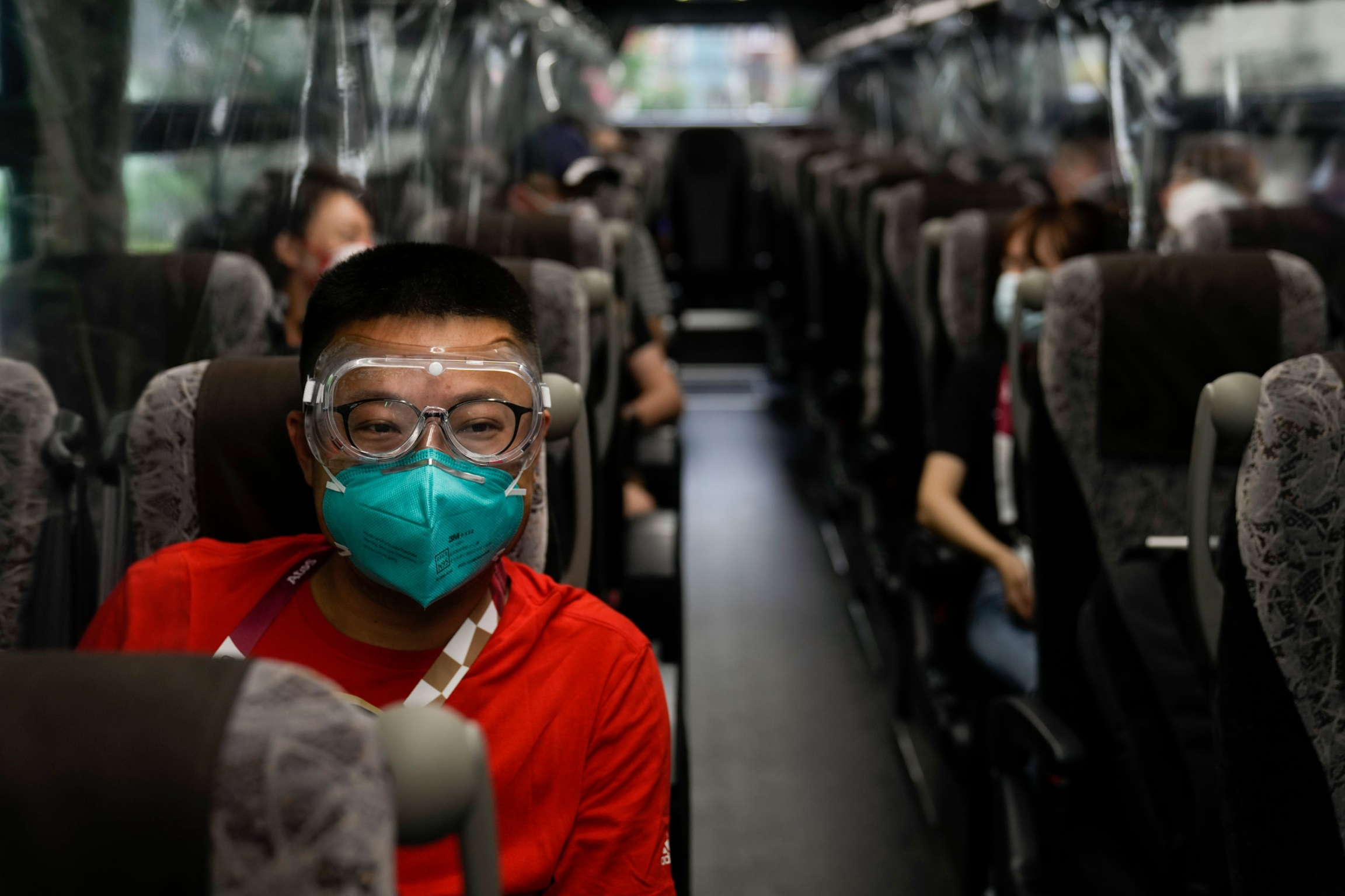 A man is shown wearing a red shirt, face mask and clear goggles while riding a bus.