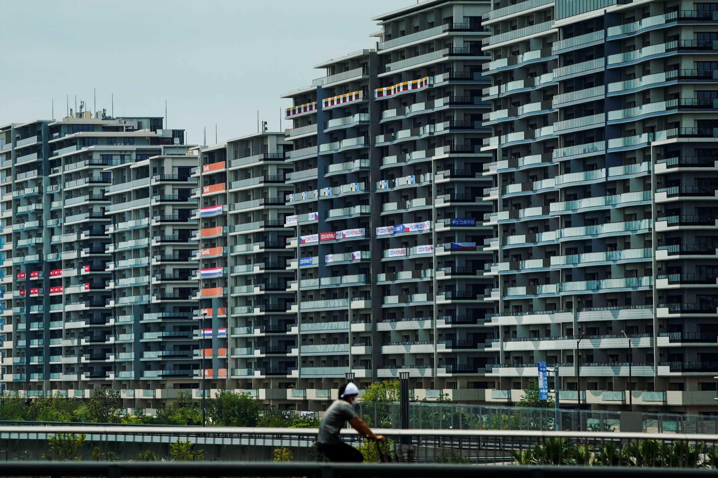 A row of tall buildings are shown, many with national flags hanging from the balconies.