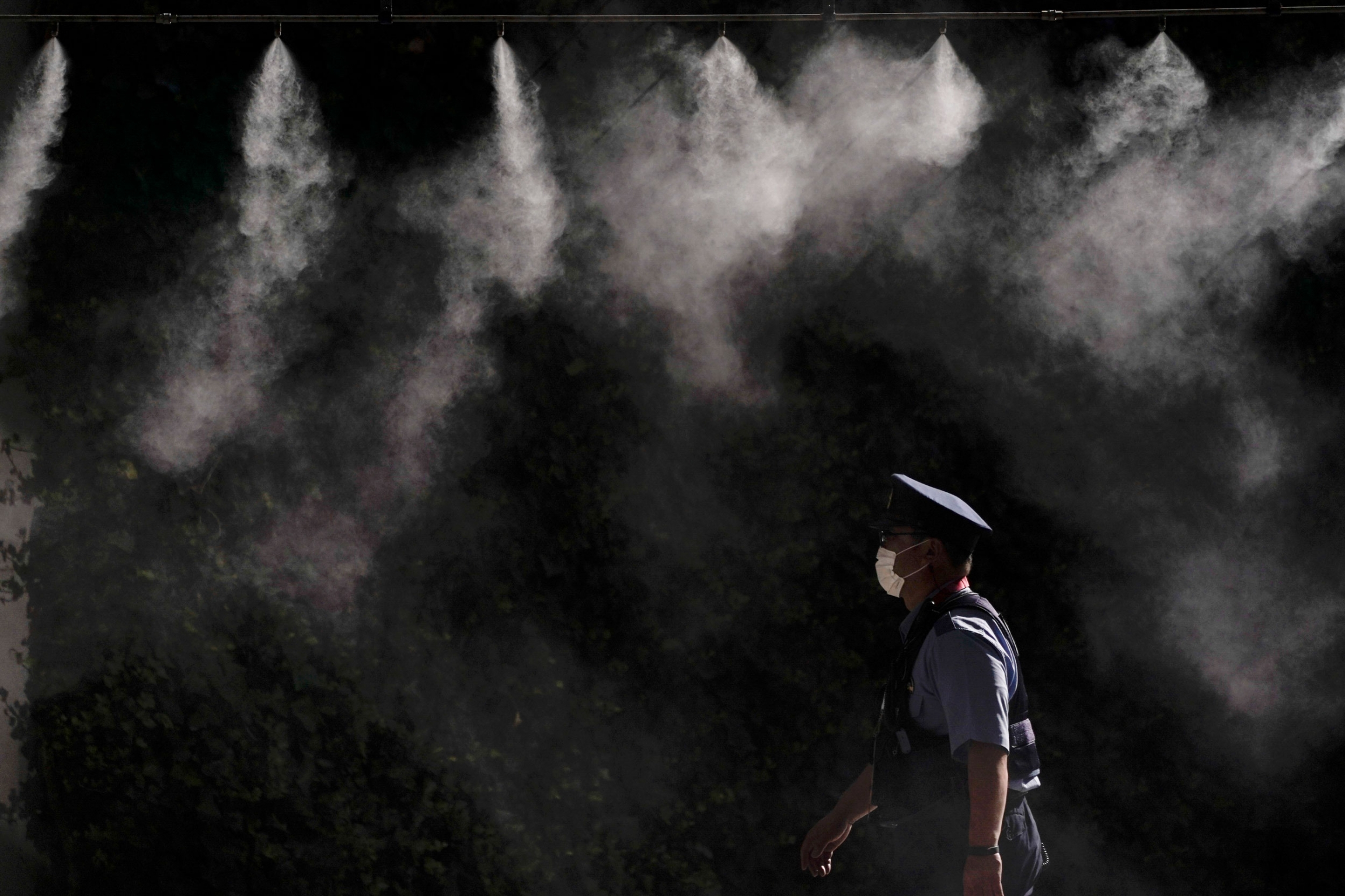 A police officer is shown wearing a white mask and walking under several misters spraying water.