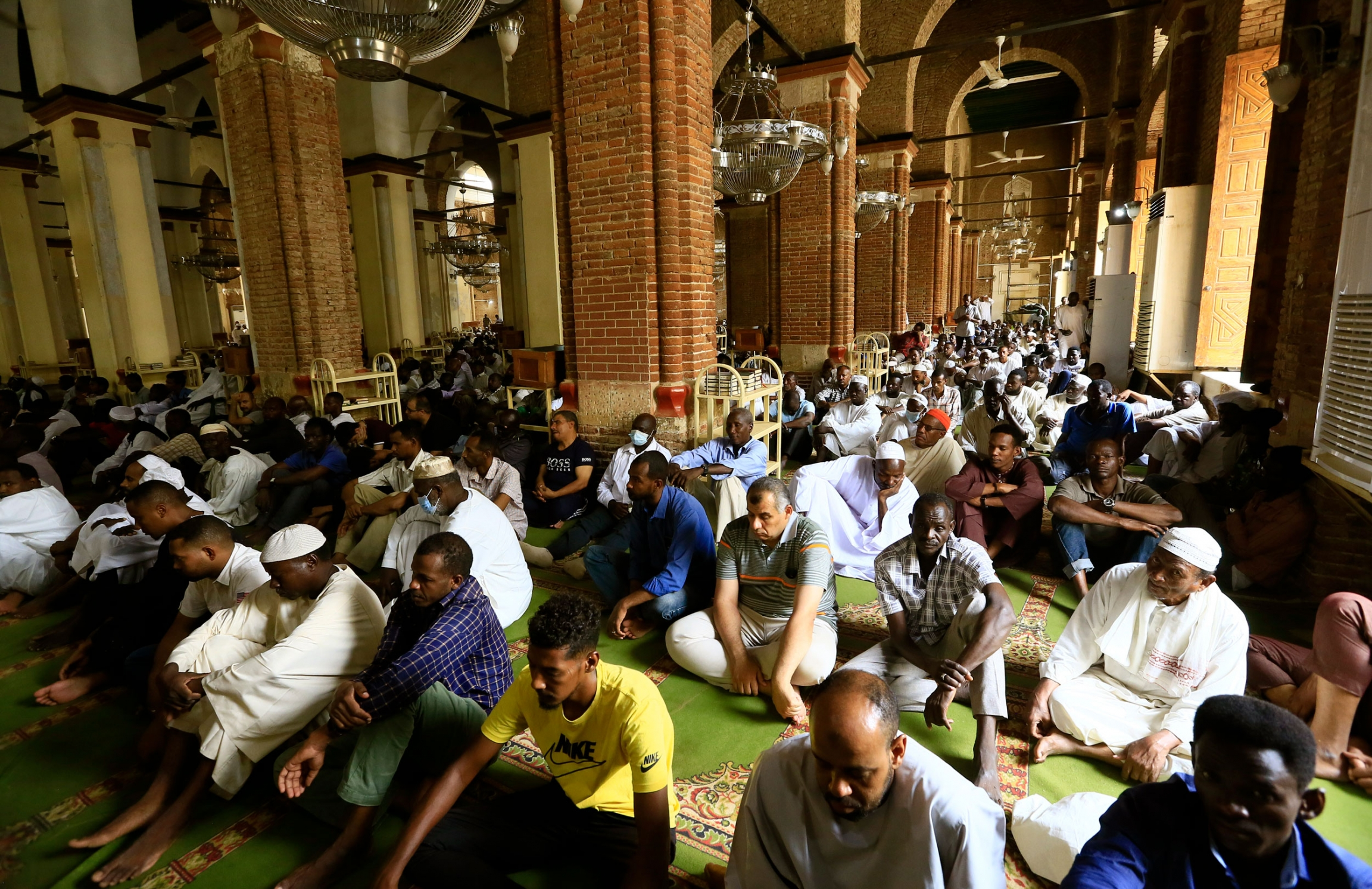 A large group of people are show sitting on the floor of the Grand Mosque with large brick columns down the middle.