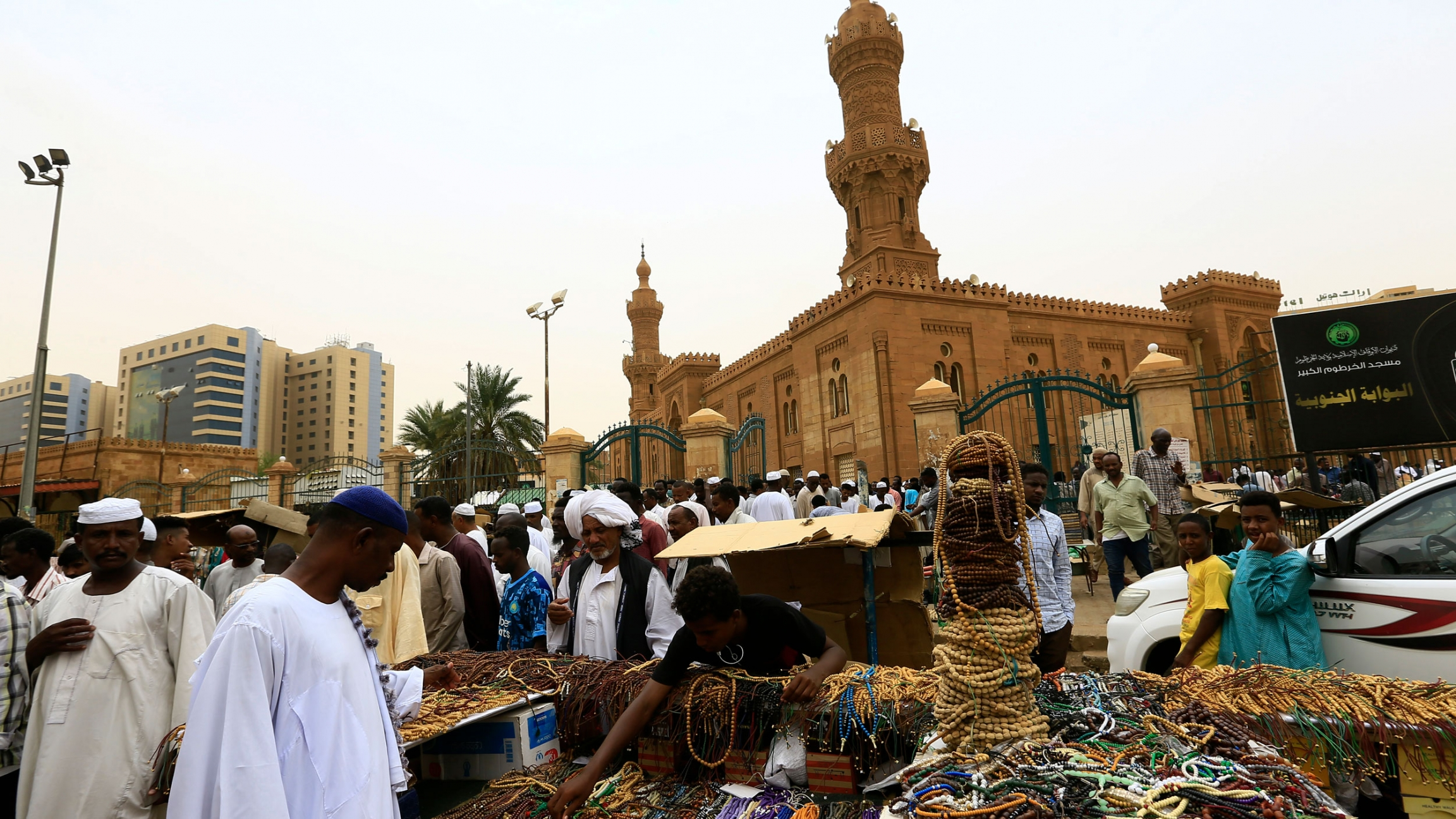 A large crowd od people are shown outside of the tan-colored Grand Mosque with a man selling beaded jewelry in the nearground.