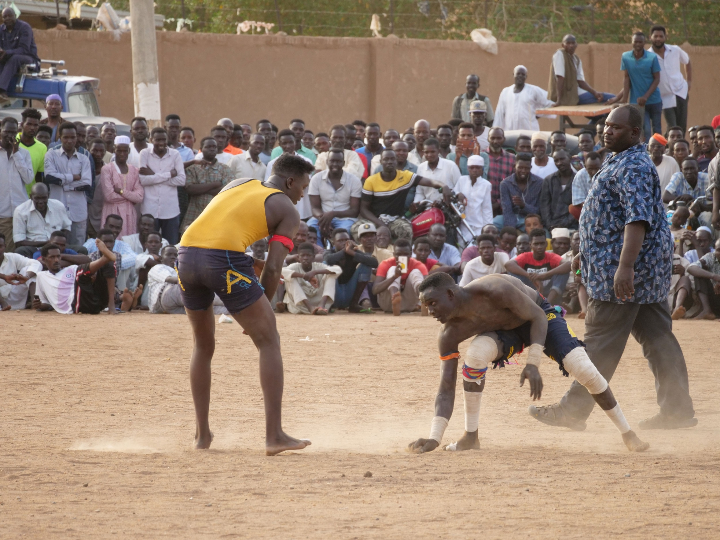 To men are shown wearing shorts and t-shirts while wrestling in a sandy courtyard.