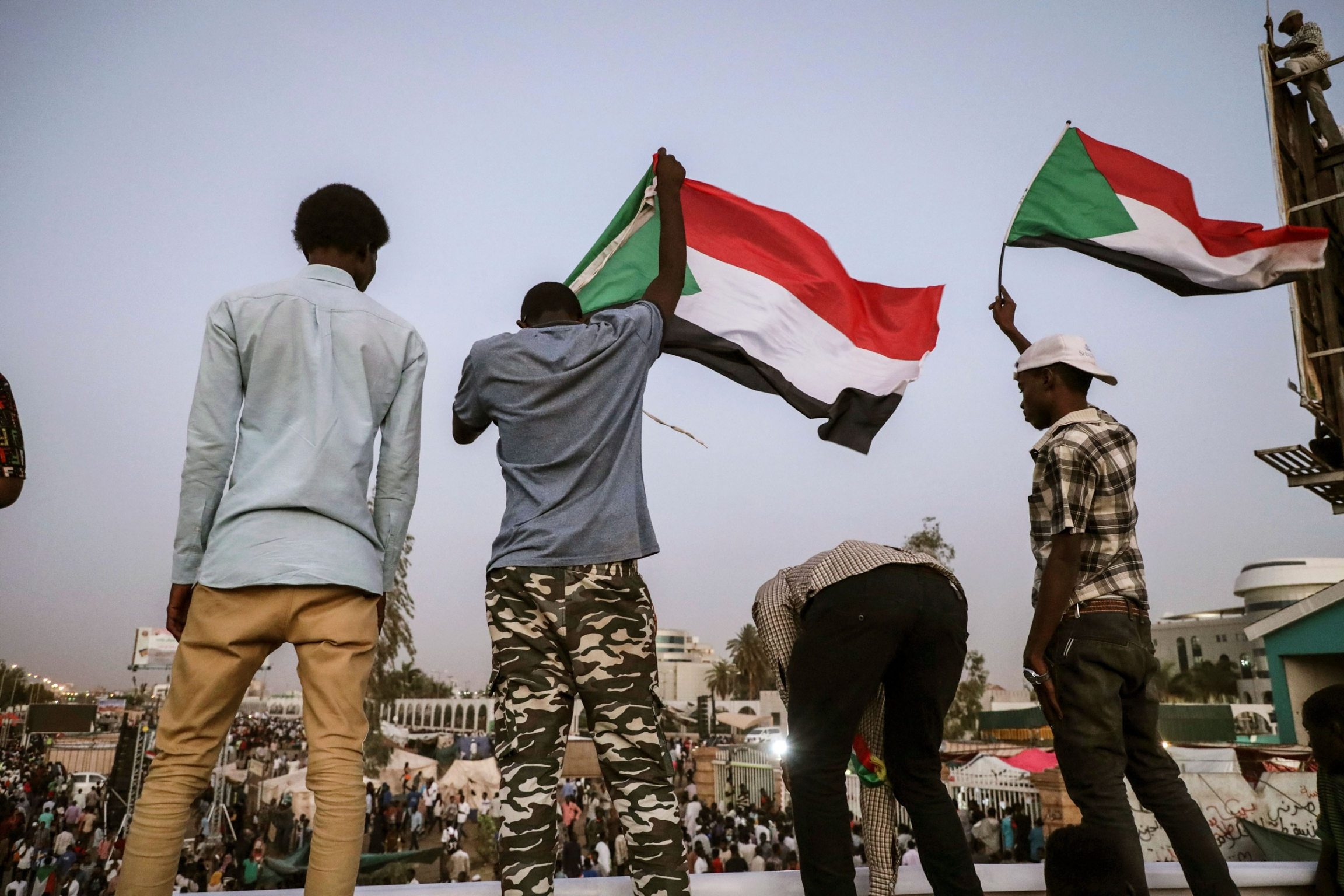 A group of four men are shown with two waving the Sudanese national flag.
