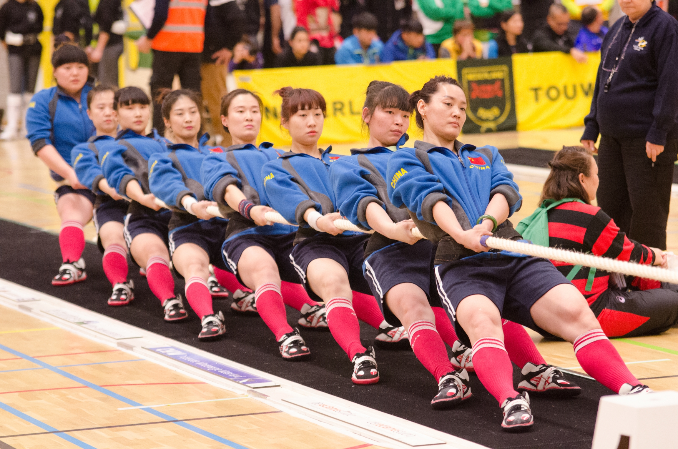 A team of women from China compete in a tug of war competition.