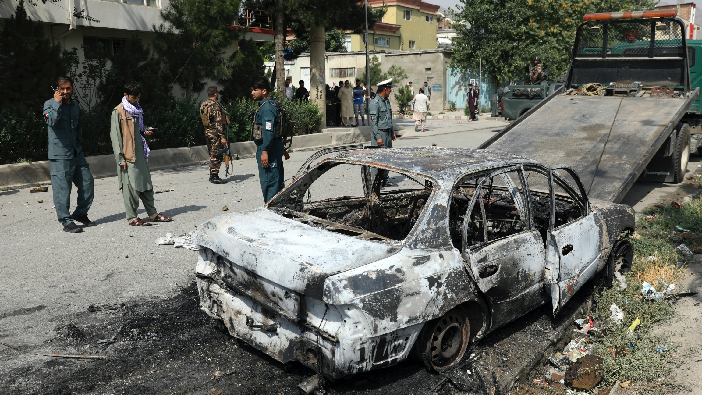 Security personnel inspect a damaged vehicle where rockets were fired from in Kabul, Afghanistan