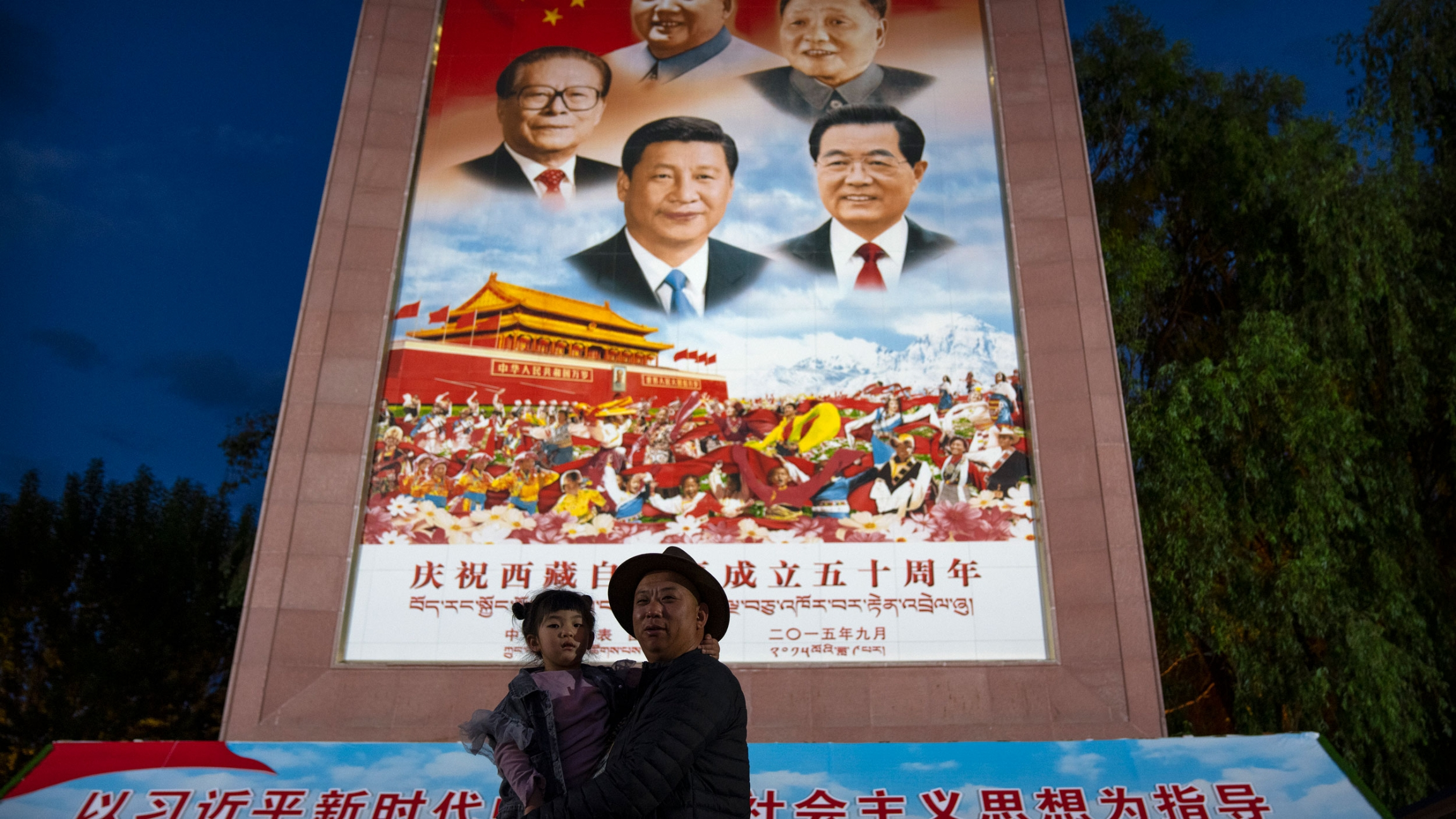 A man holds a girl as they pose for a photo in front of a large mural depicting Chinese President Xi Jinping, bottom center, and other Chinese leaders at a public square at the base of the Potala Palace in Lhasa in western China's Tibet Autonomous Region