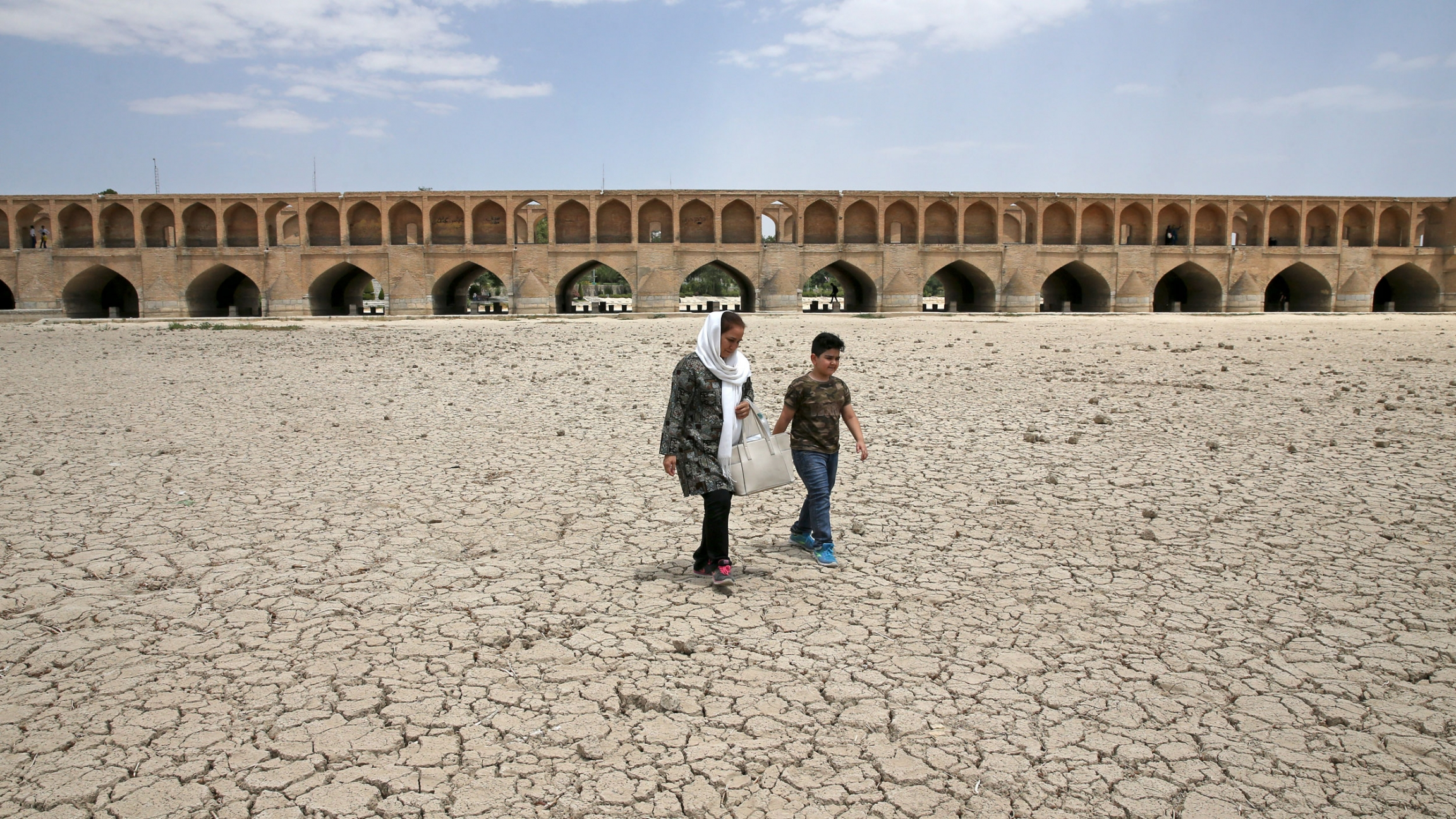 A woman and a boy walk on the dried up riverbed of the Zayandeh Roud river that no longer runs under the 400-year-old Si-o-seh Pol bridge, named for its 33 arches, in Isfahan, Iran