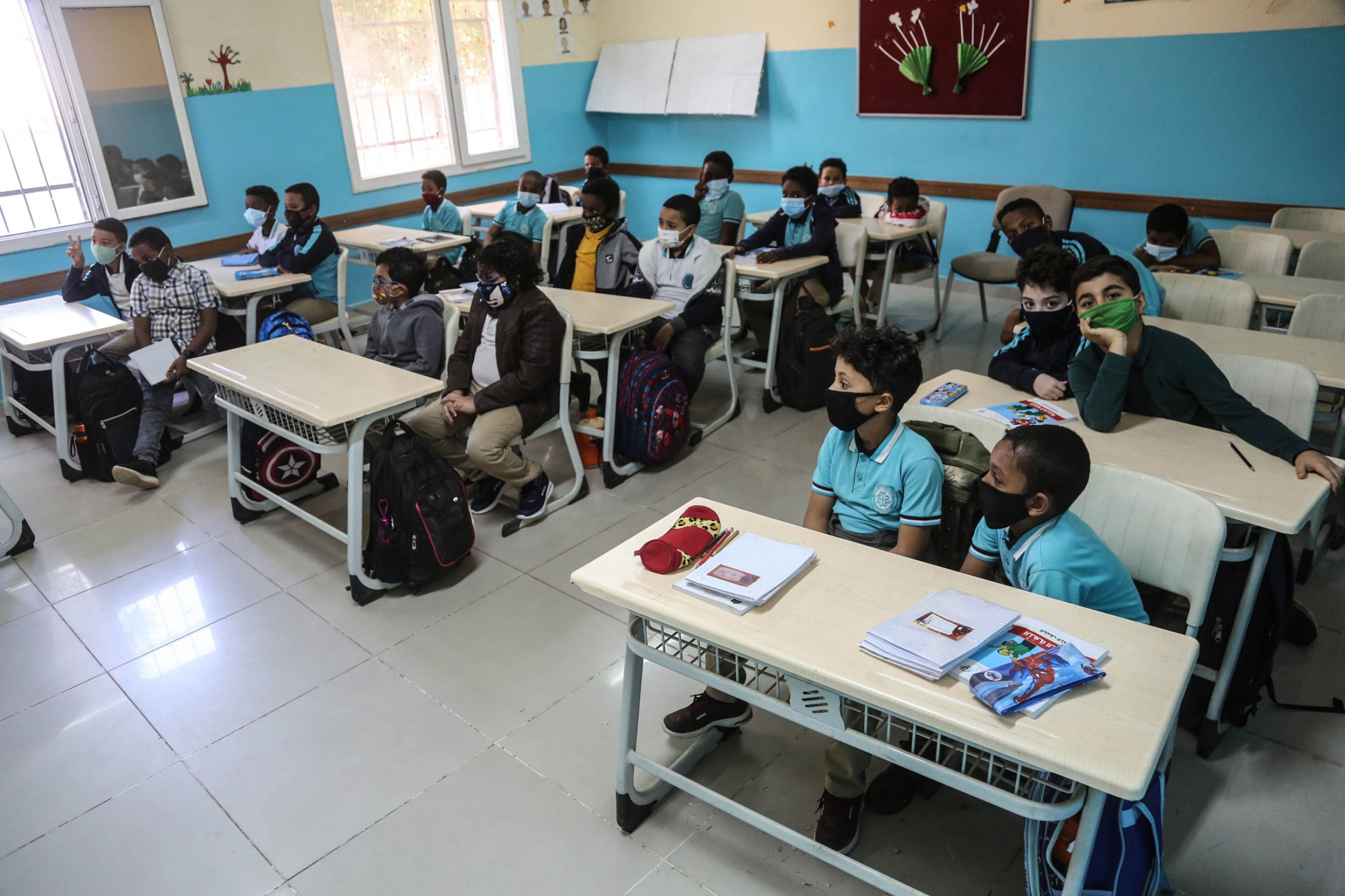 Three rows of desks are shown with two students sitting at each desk in a classroom with blue and white walls.