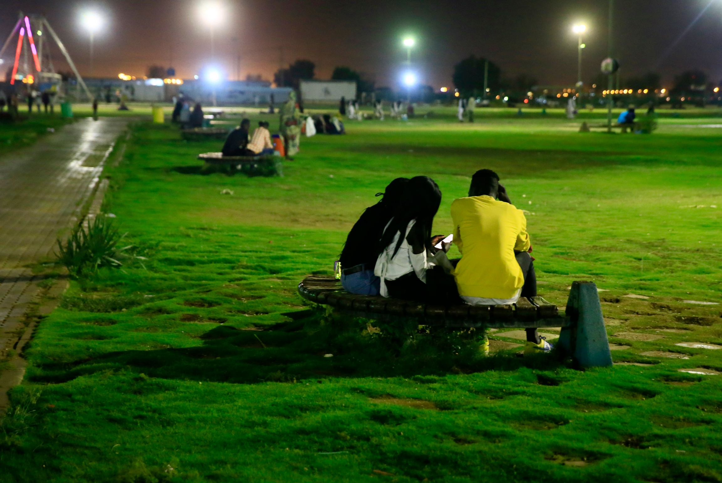 Three people are shown with one person wearing a yellow shirt while sitting on a curved metal bench amid a large grassy area.