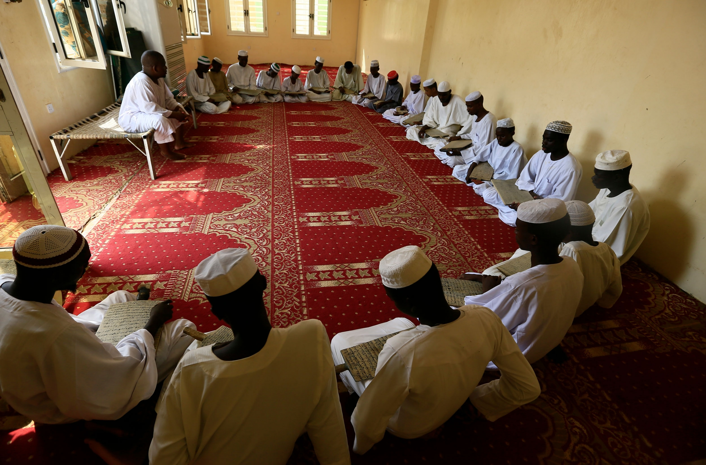 A large group of young men are shown sitting in a half circle on the ground and holding wooden boards with Islamic text.