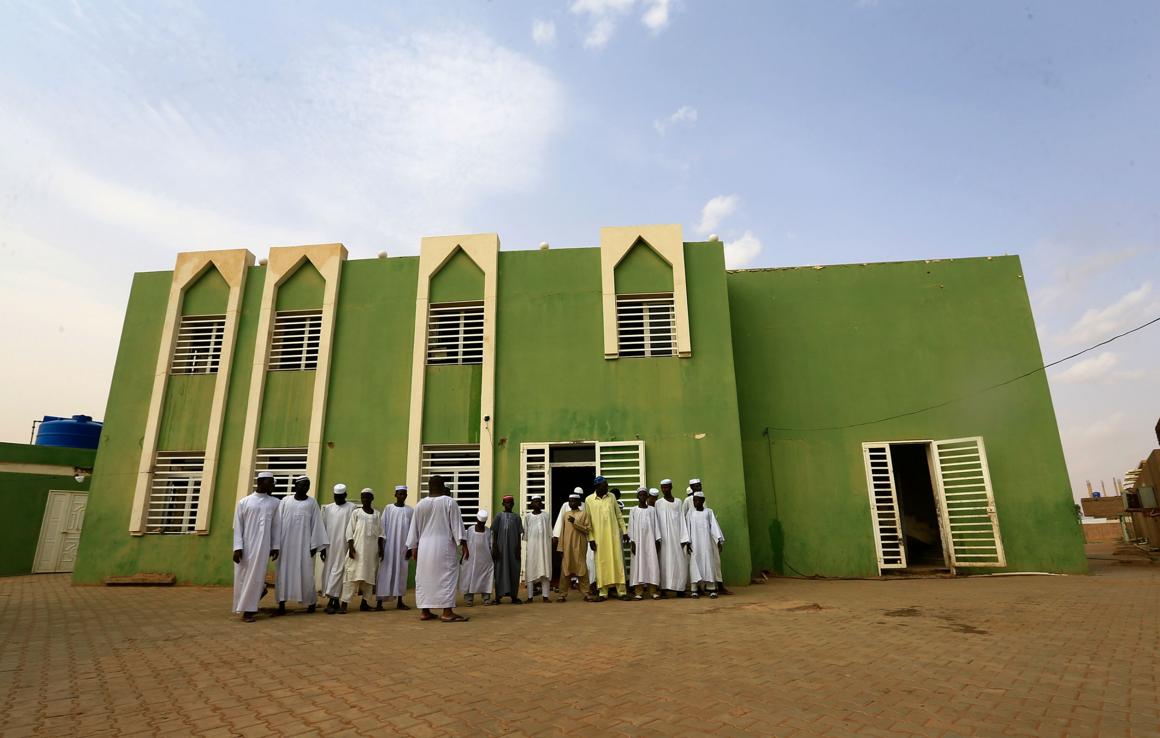 A group of men are shown in traditional Islamic robes outside of the green facade of the Haj Yousif Mosque.