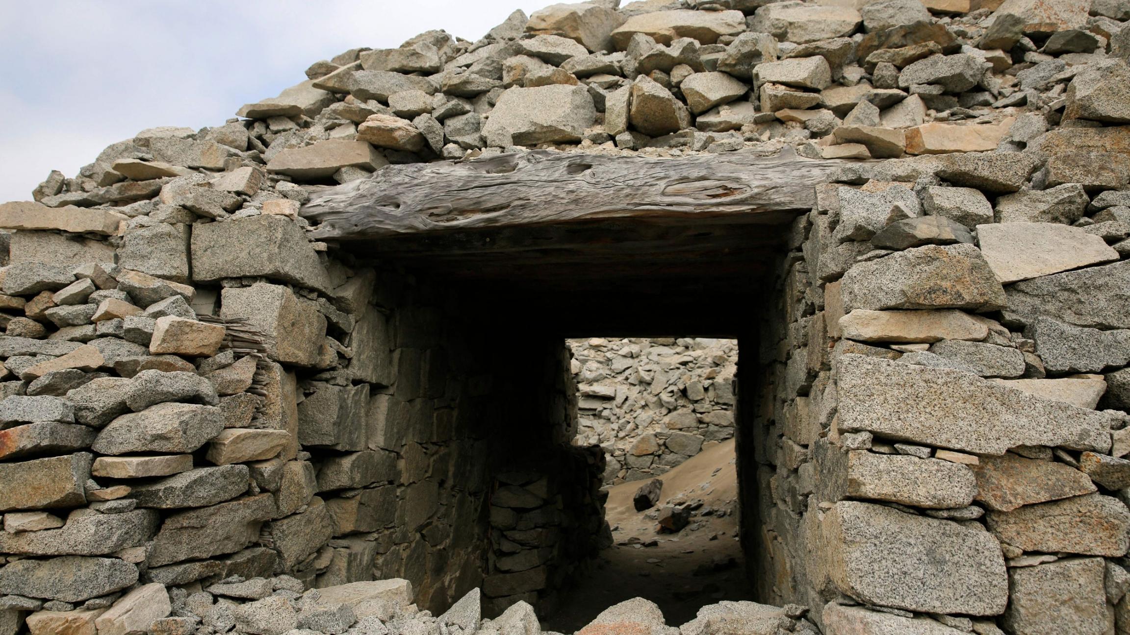 A large pile of stones are shown with a square opening and a passageway.