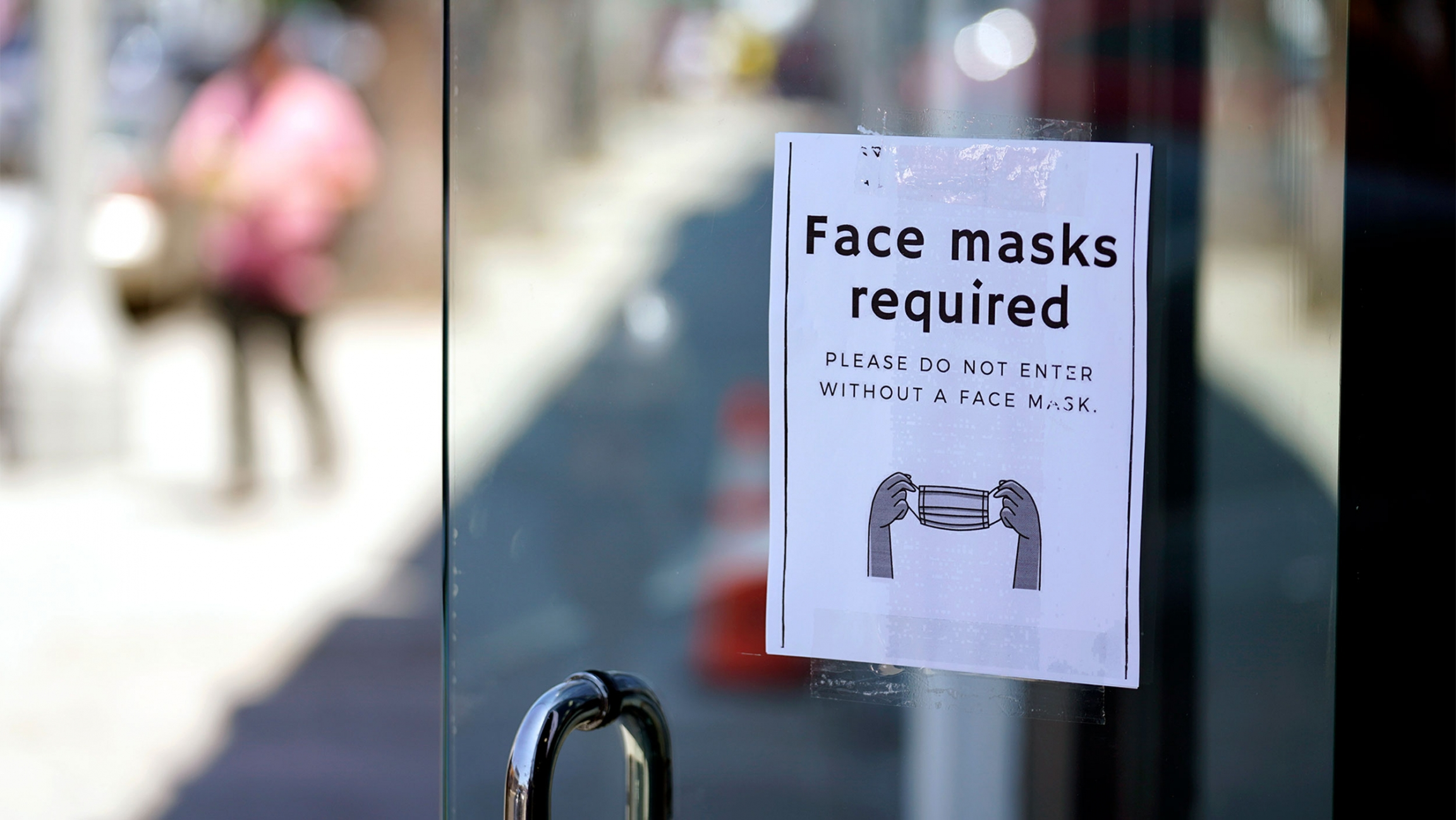 """Door with a """"face masks required"""" sign and a person blurred in the distance"""