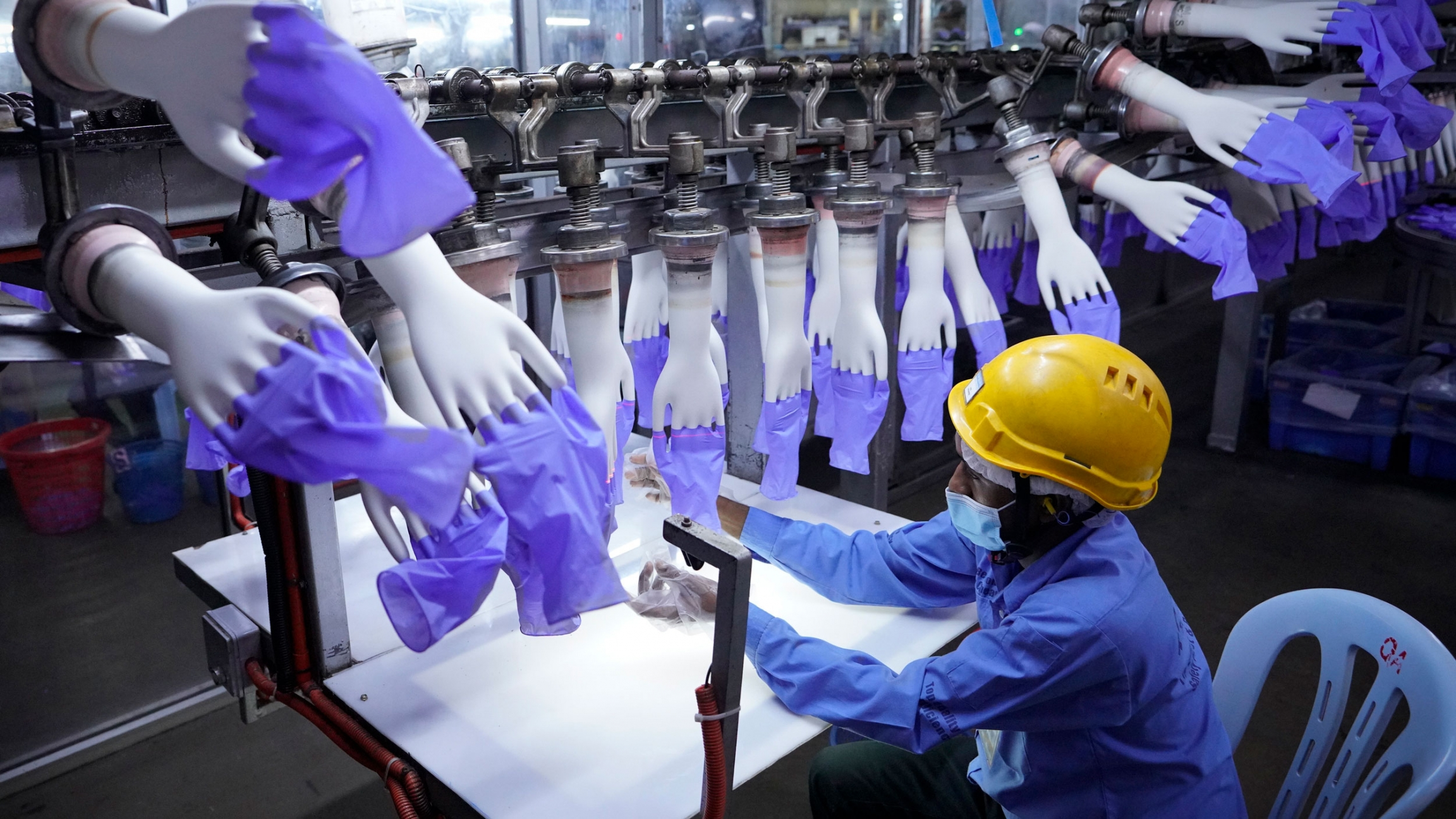 A worker wearing a yellow safety hat inspects disposable blue gloves at a factory.