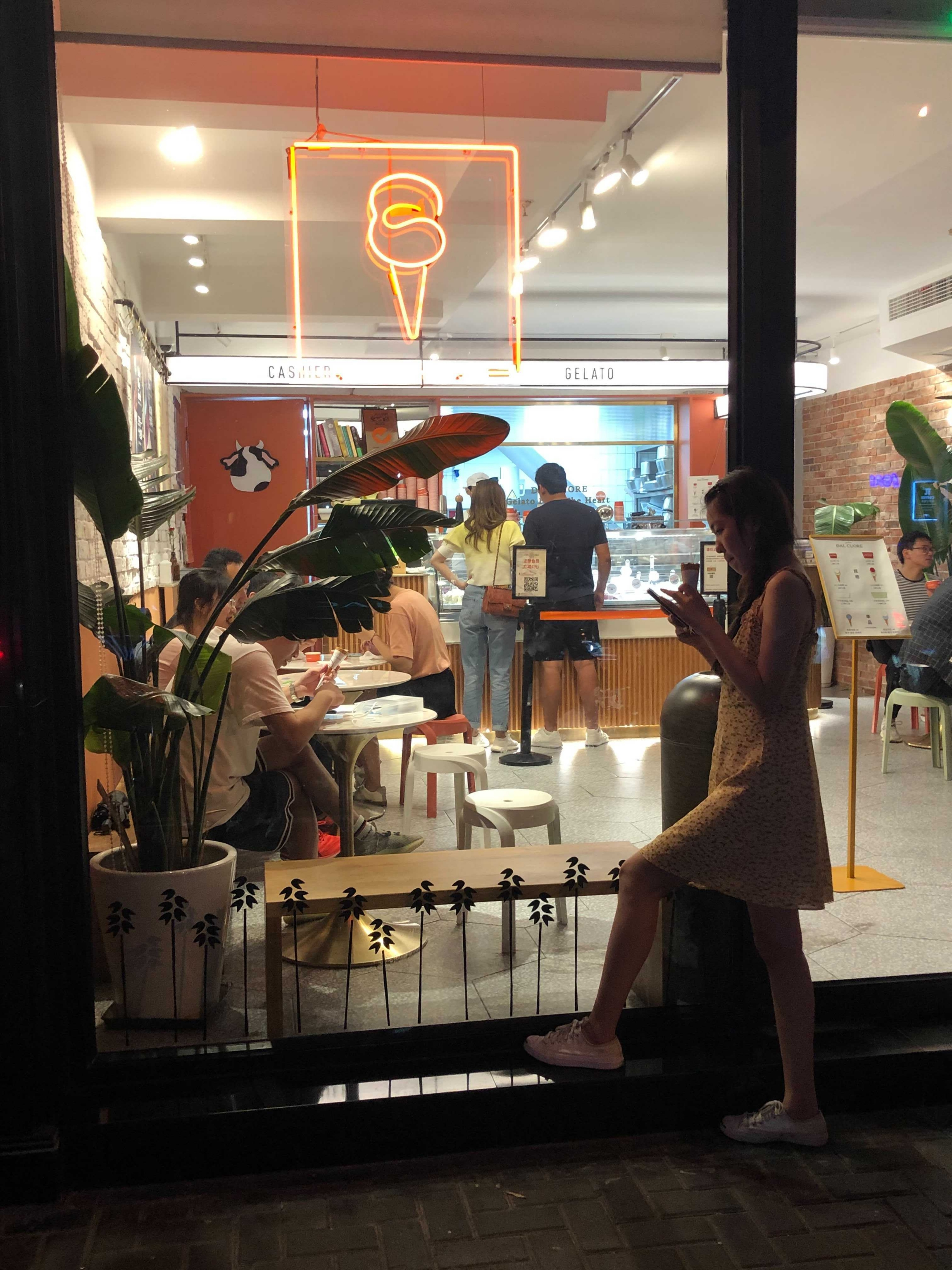 Woman stands outsideGelato Dal Cuore ice cream shop and customers order inside
