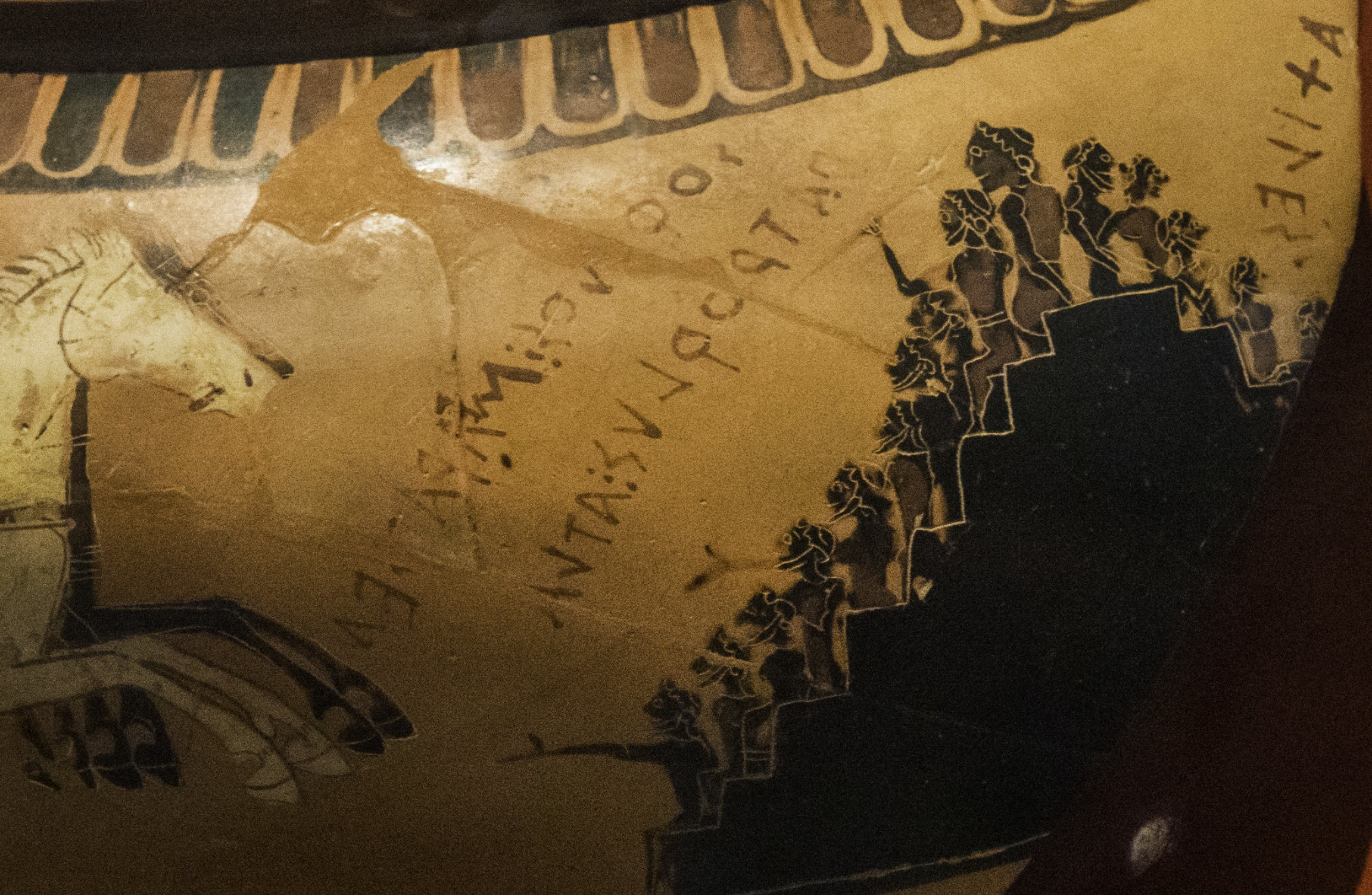 A detail of a Greek cauldron depicts spectators cheering on a chariot race.