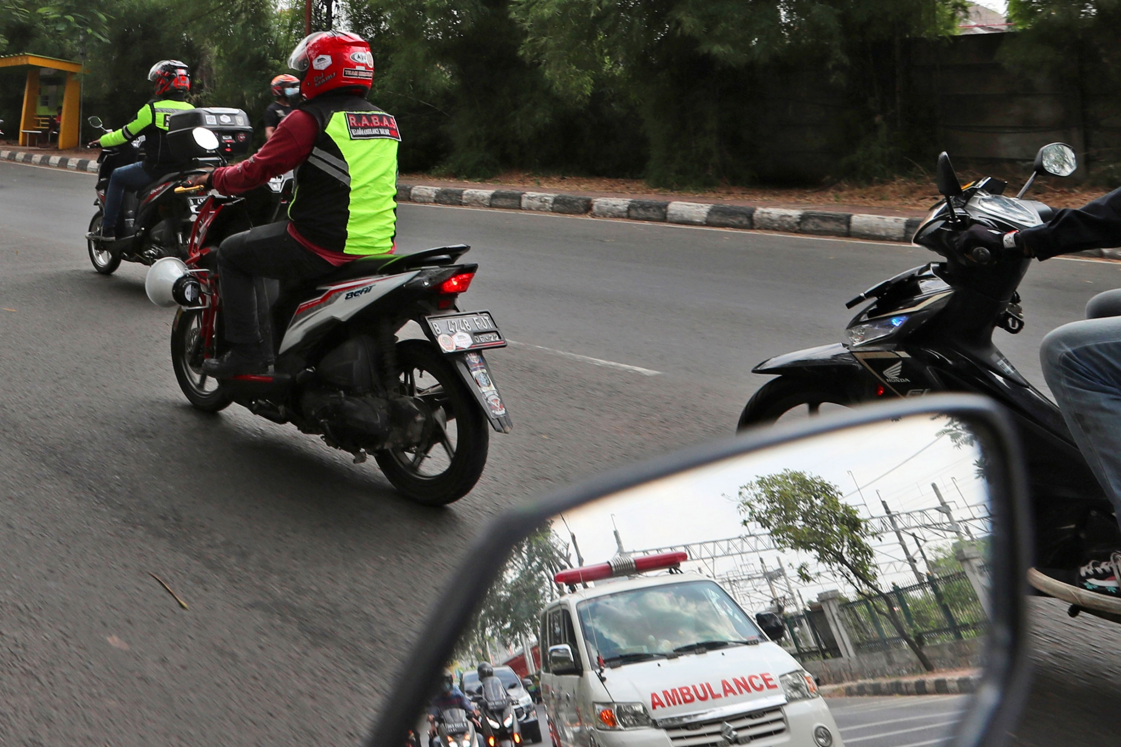 An ambulance is shown in the reflection  of a motorbike's side view mirror.