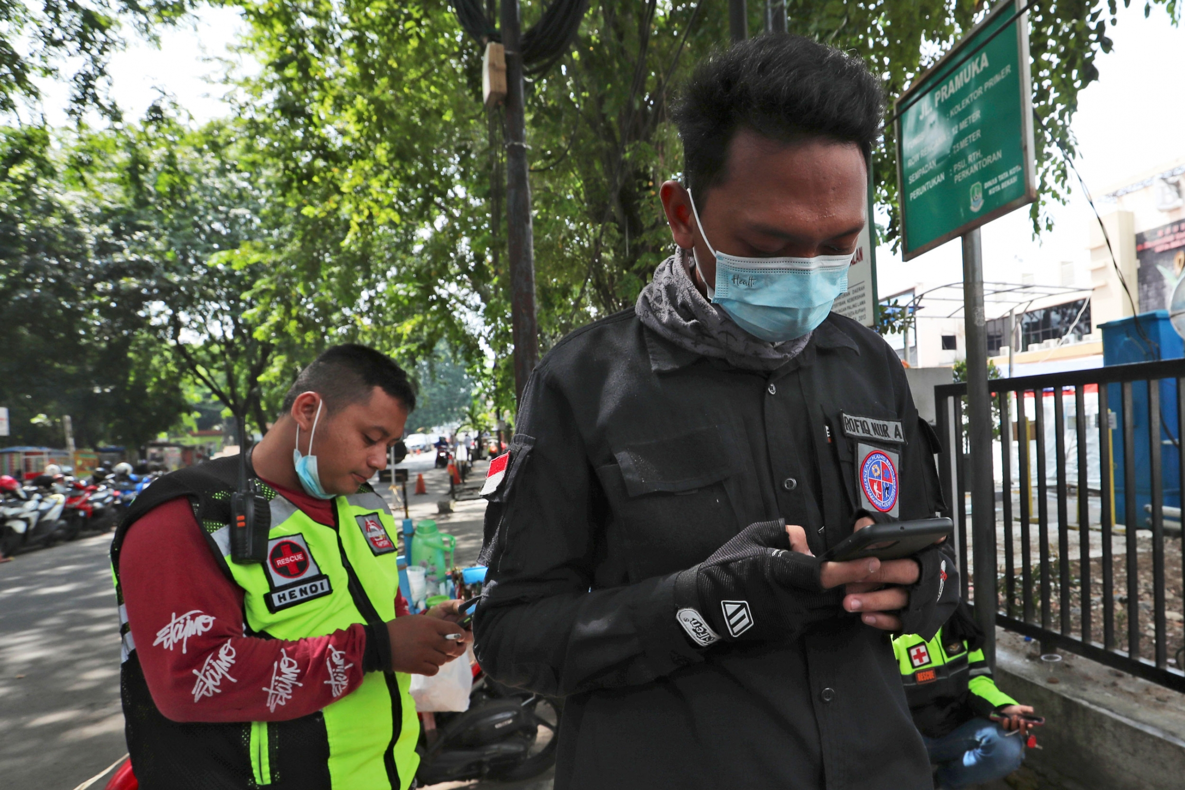 Two men are shown looking down at their mobile phones while wearing medical face masks.