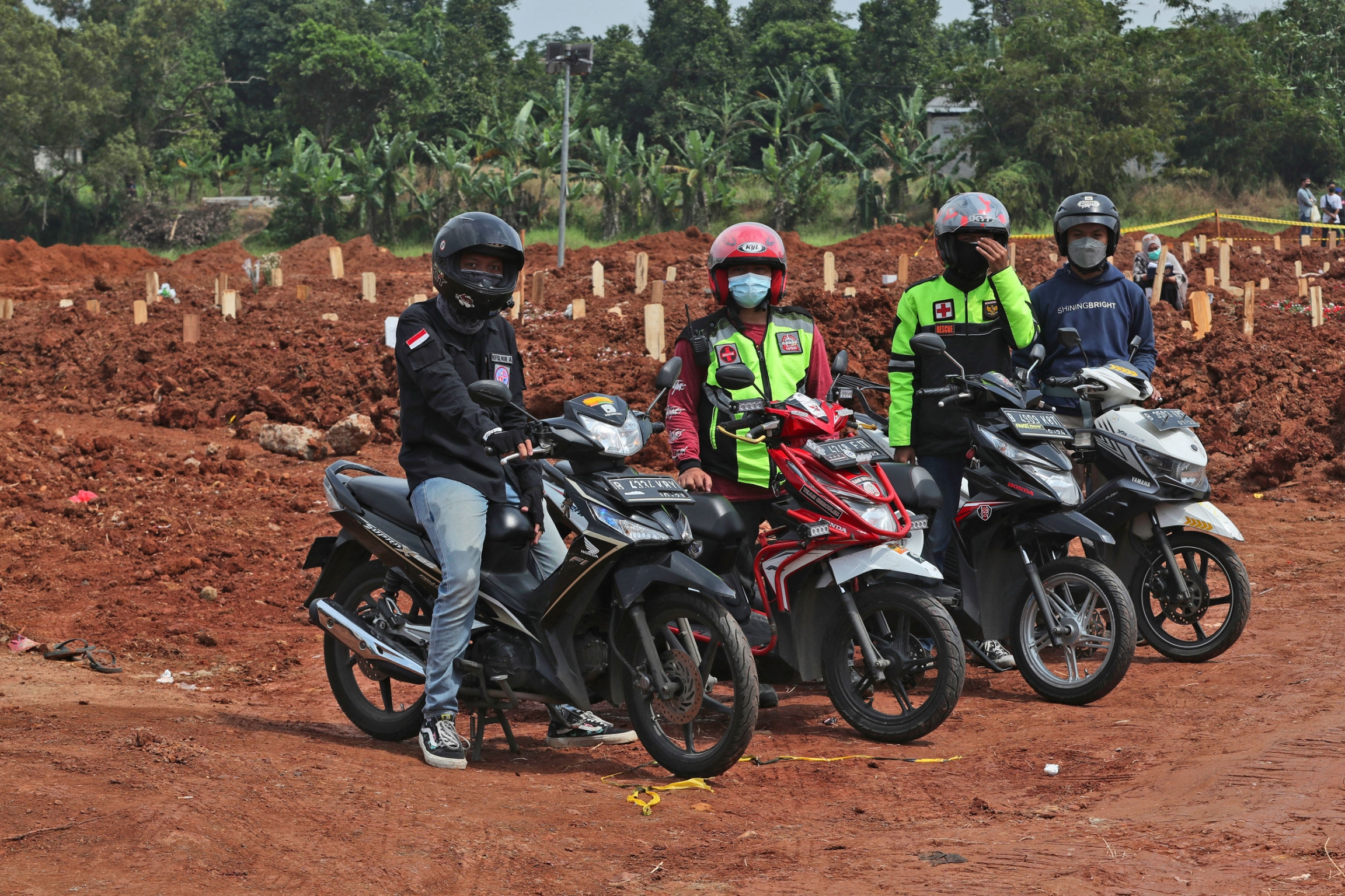 Four people are shown sitting or standing next to motorbikes with a cemetary in the background.